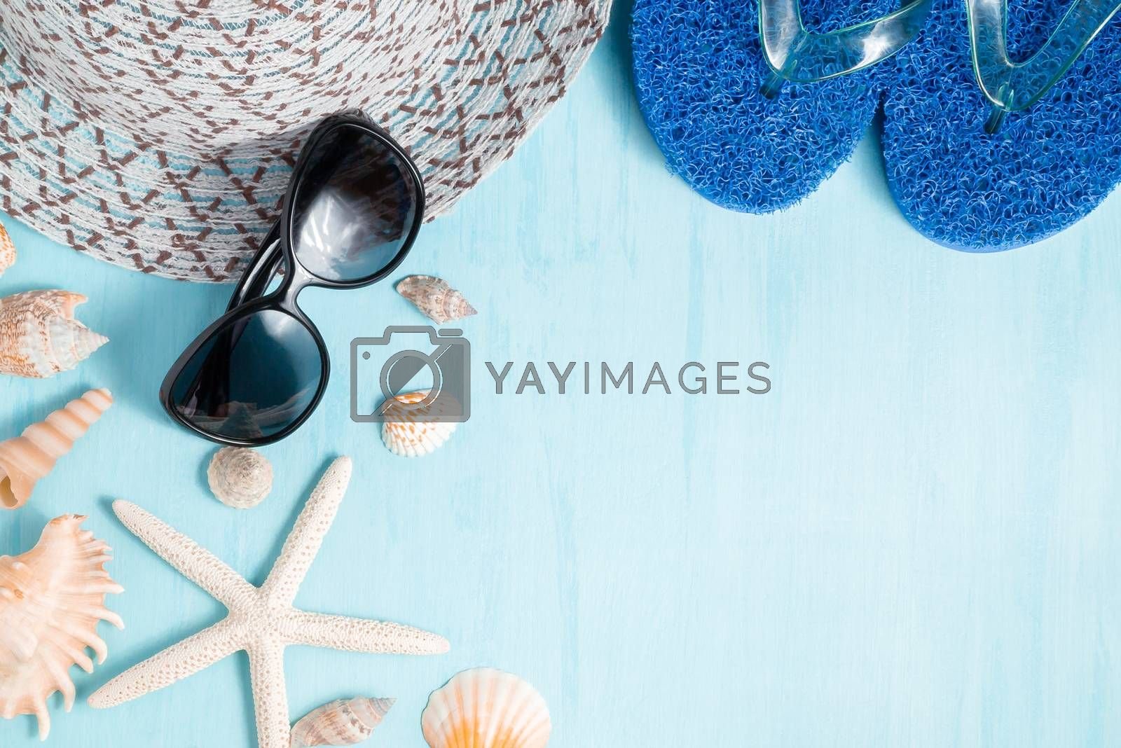 Blue sea background with hat, sunglasses and seashells, summer holiday and vacation time concept by galsand