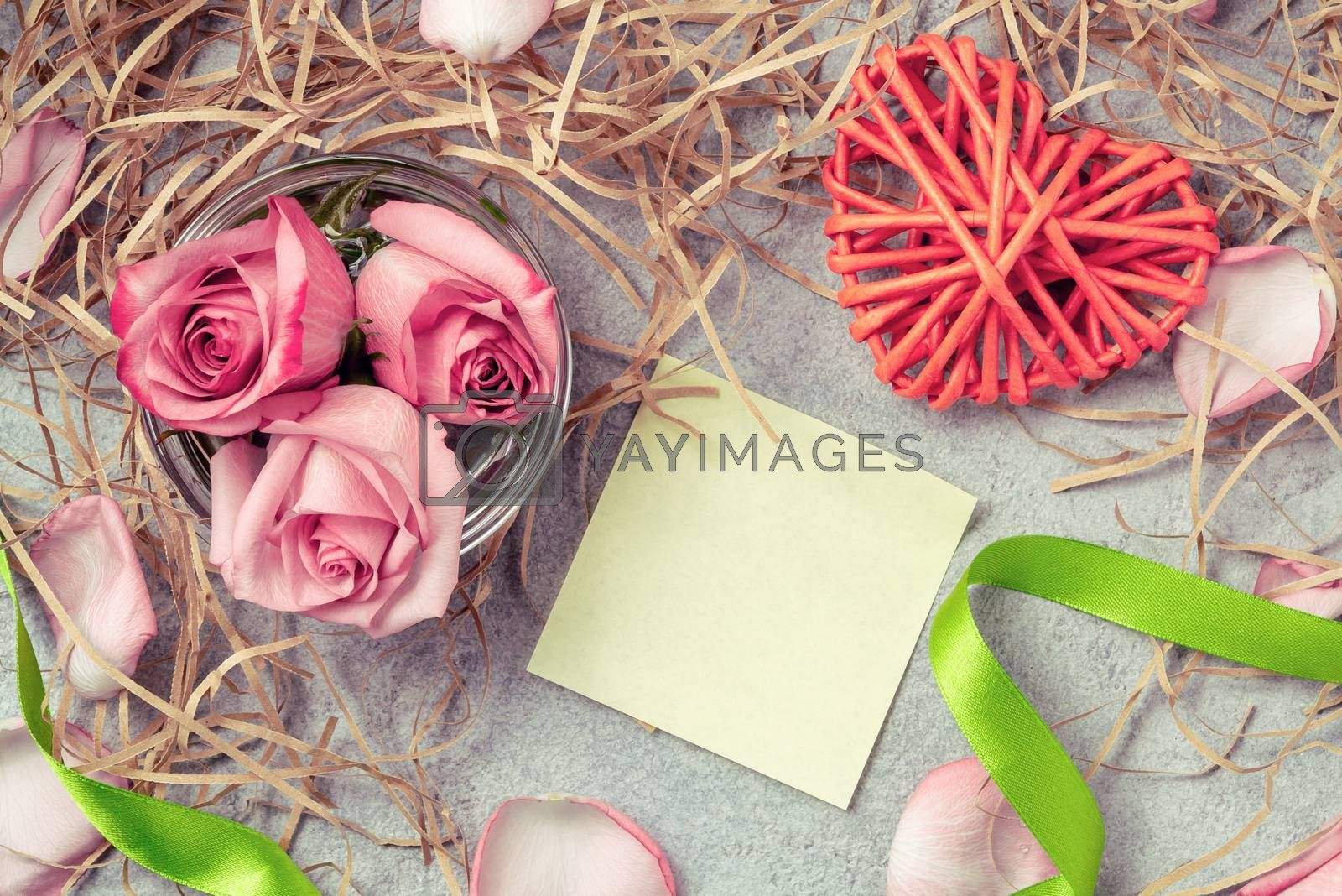 Pink roses in the water, a wicker heart, ornaments and an empty form for a note on the table by galsand