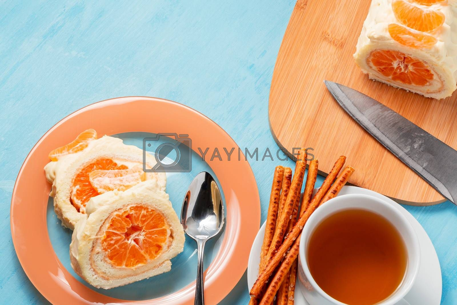 Sweet roll with whipped cream and tangerine filling and a cup of tea by galsand