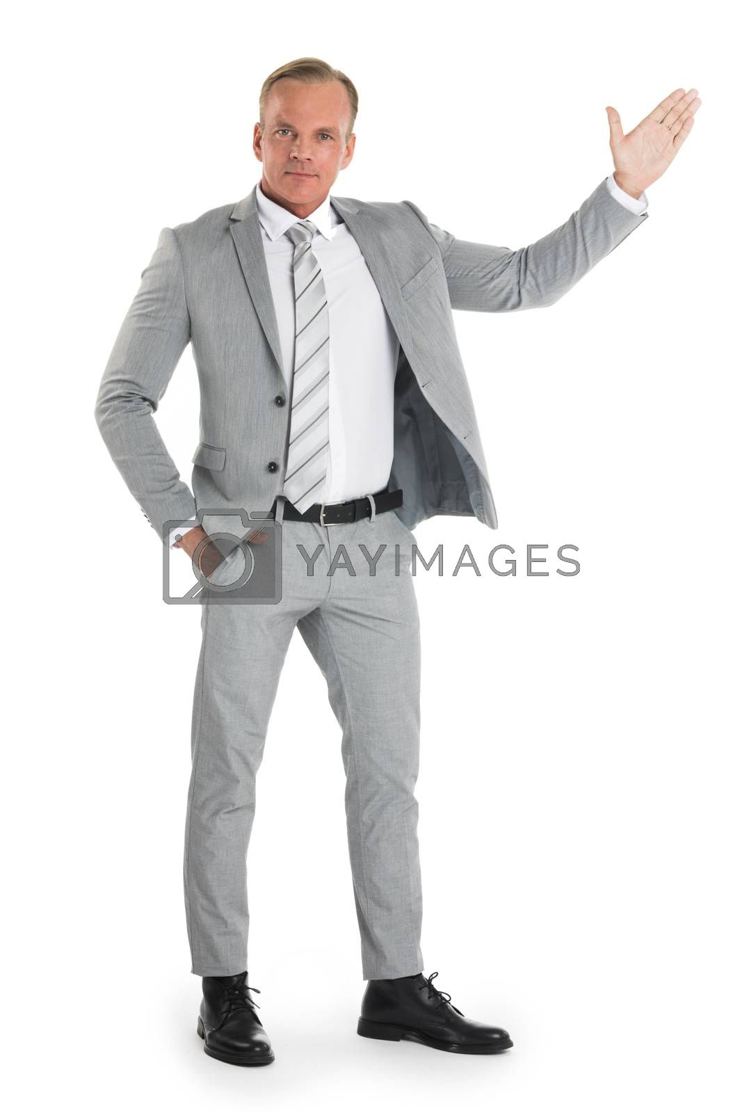 Businessman pointing with hand palm at empty copy space, studio isolated on white background, full length portrait
