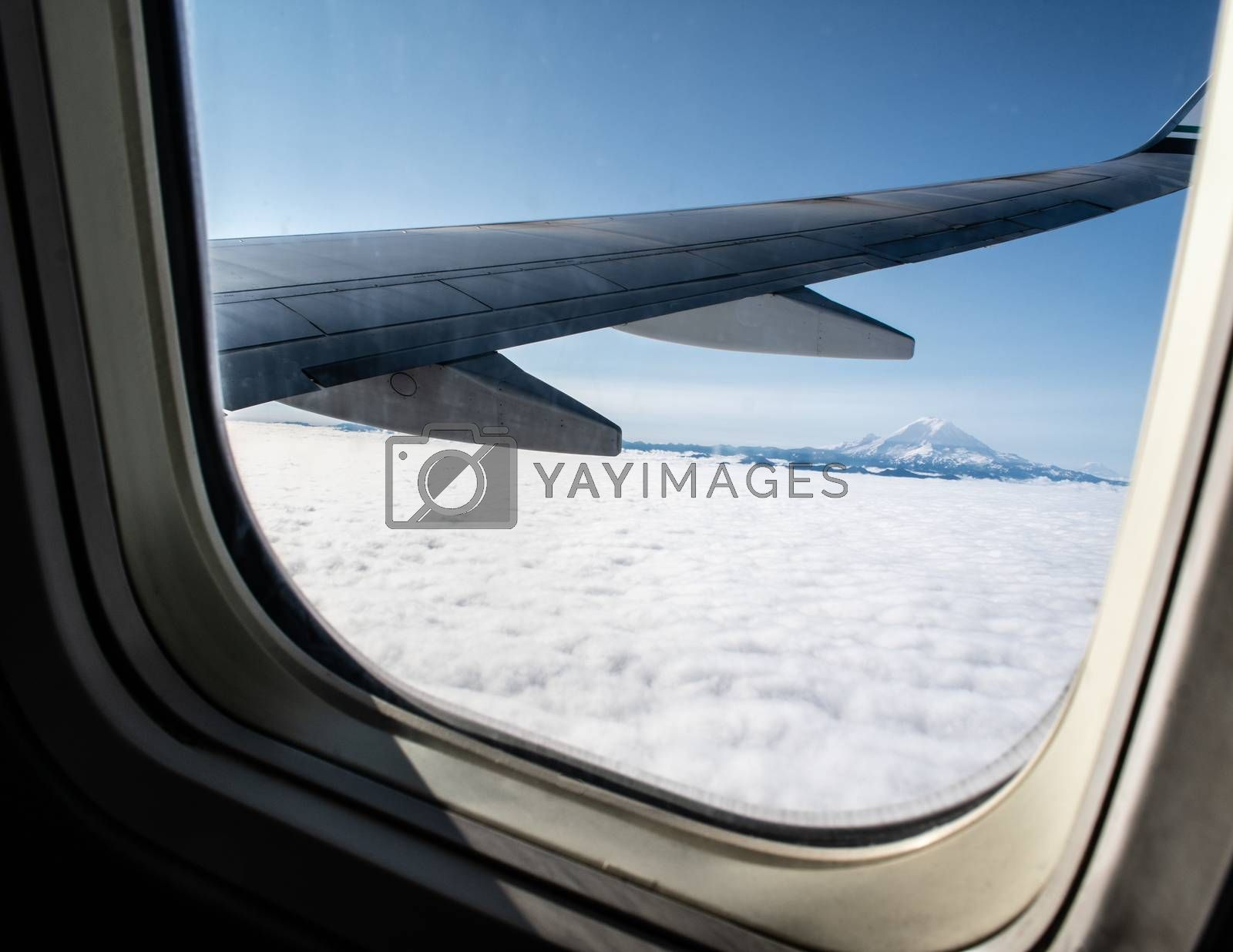 Airplane wing and cloudy mountain views from window seat of a plane