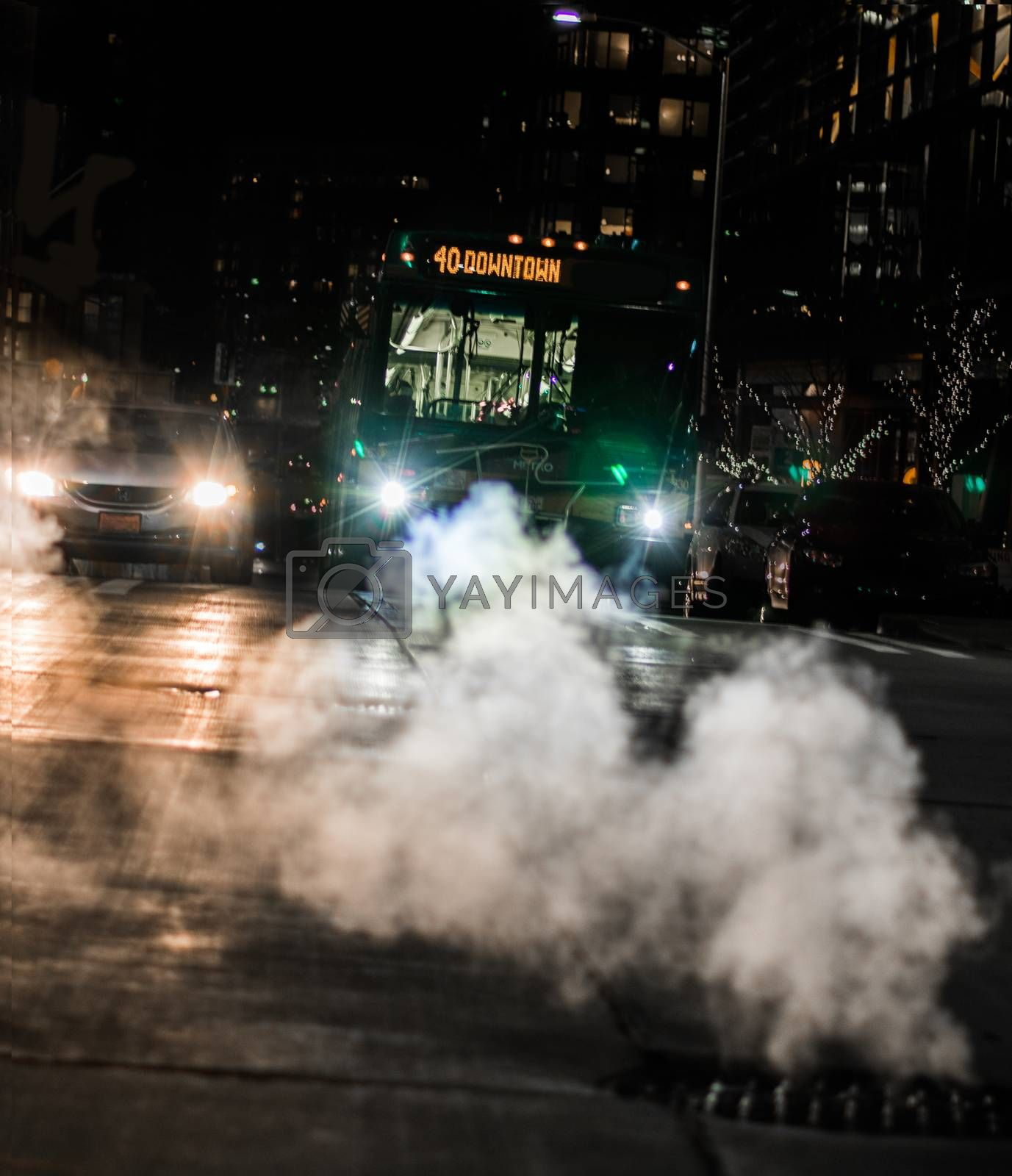 Bus and car at intersection with steam rising from a sewer
