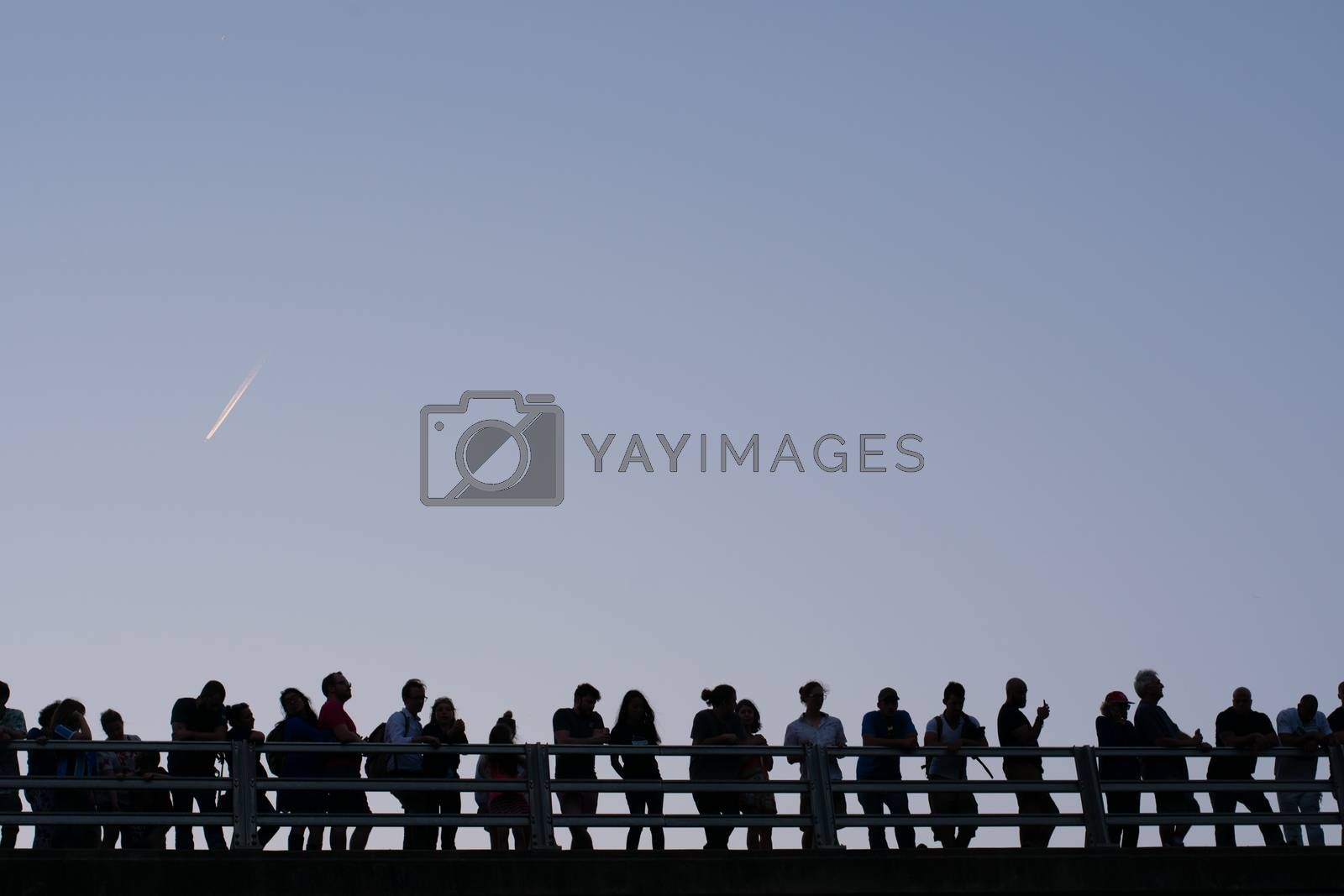 Silhouettes on a bridge with blue sky background