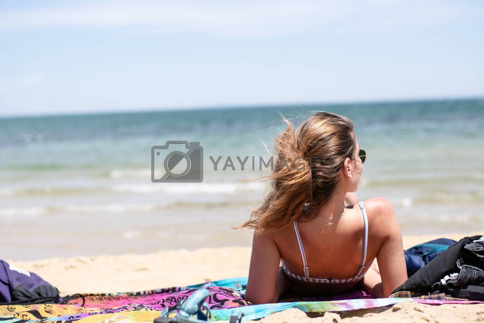 Girl laying on beach towel in sunlight on summer day