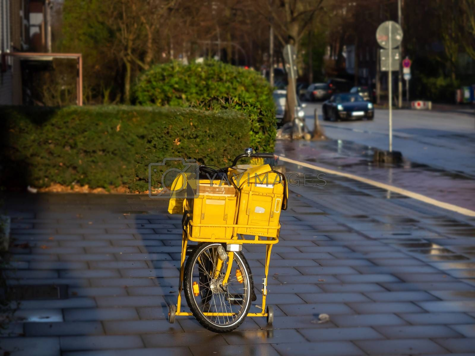 A yellow bicycle from the postman, alone in the street by Sandra Fotodesign