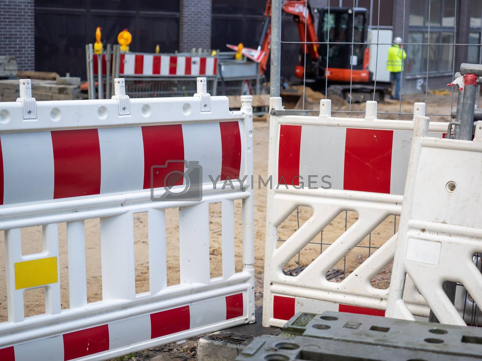 A red white barrier of a construction site in the city by Sandra Fotodesign