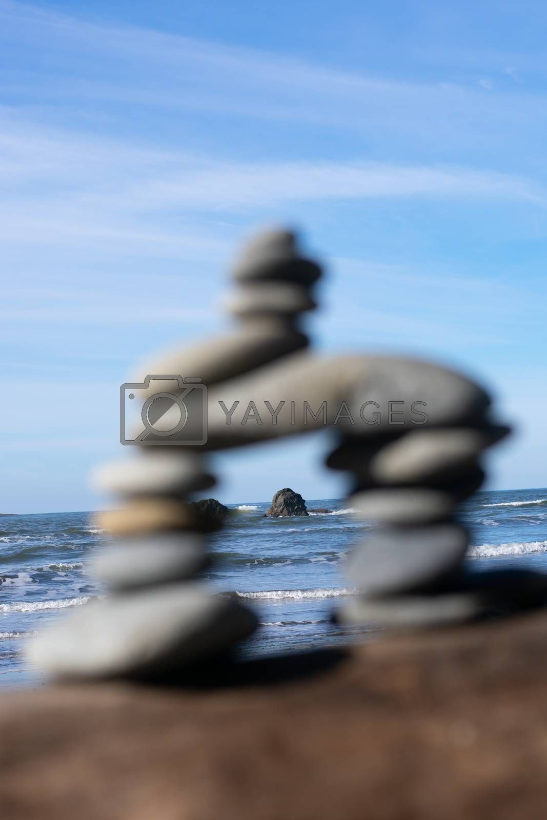Rock tower sitting on log on the beach with ocean background