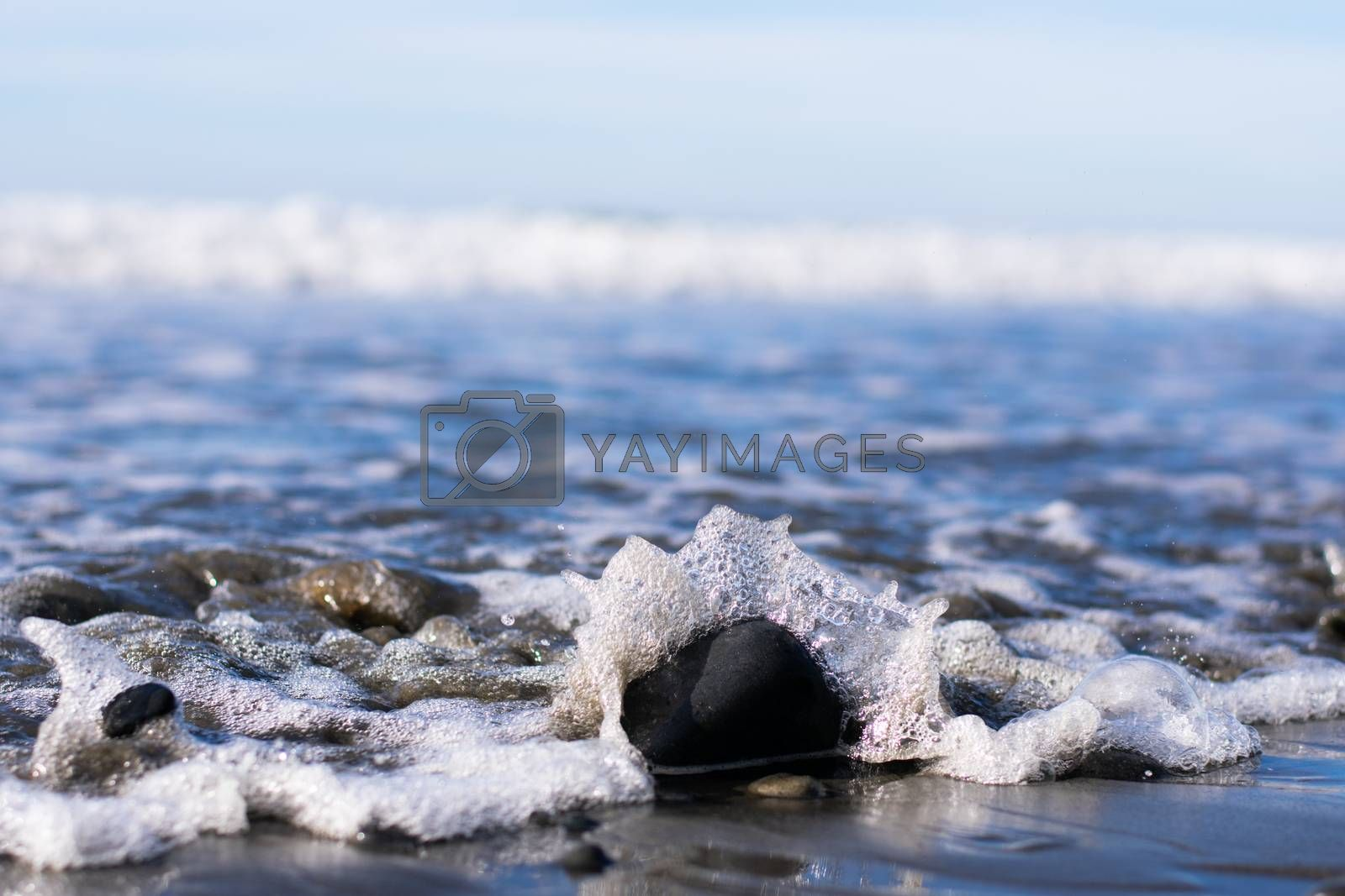 Waves crashing on a rock with sea foam and blue sky background