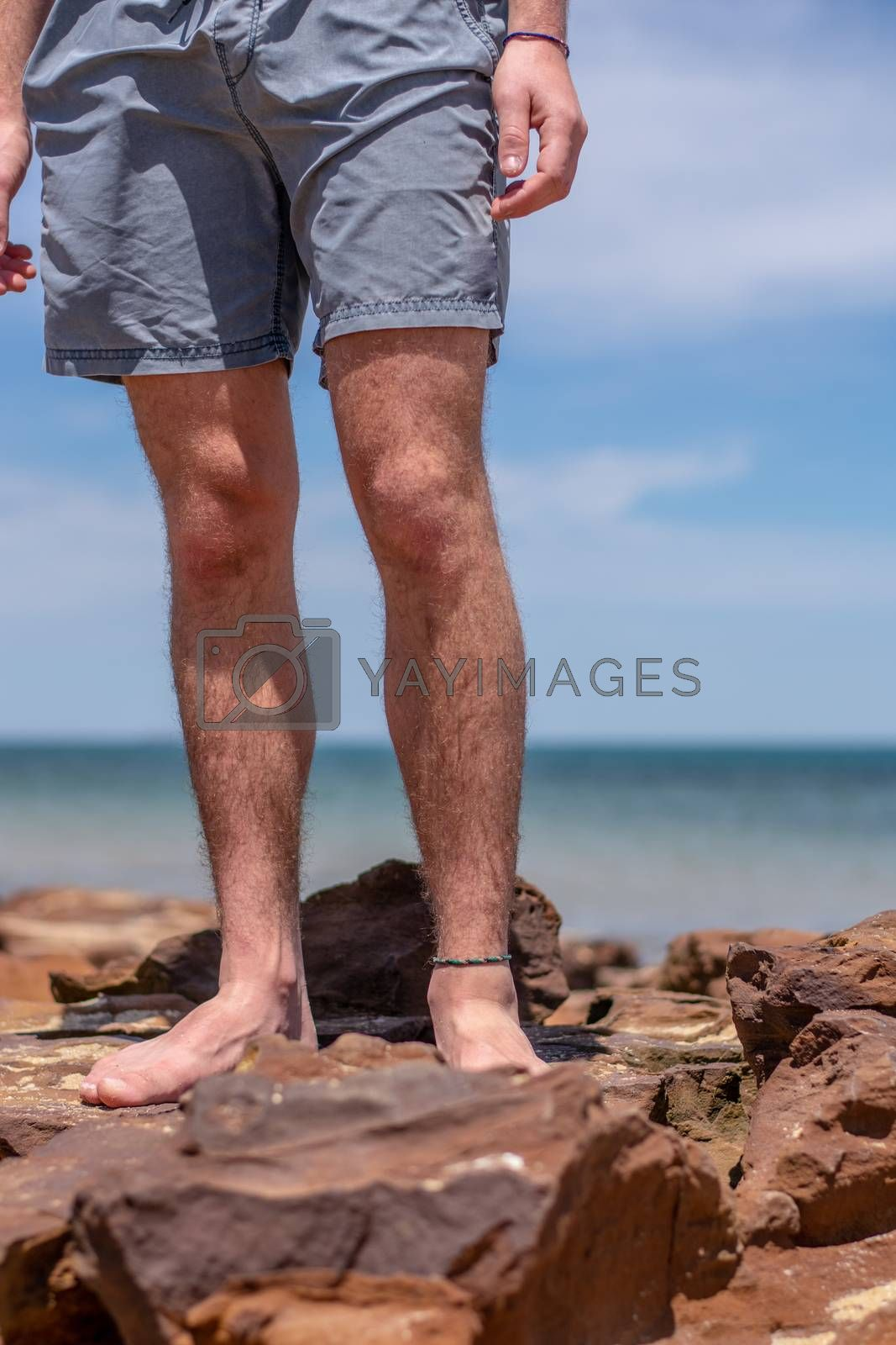 Man's hairy legs on a rocky beach with view of the ocean and sunny blue sky