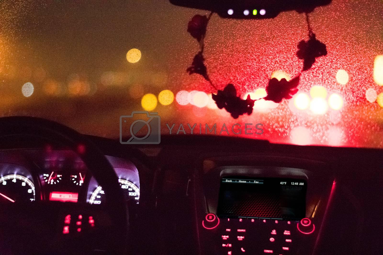 Red brakelights illuminating rain droplets on windshield