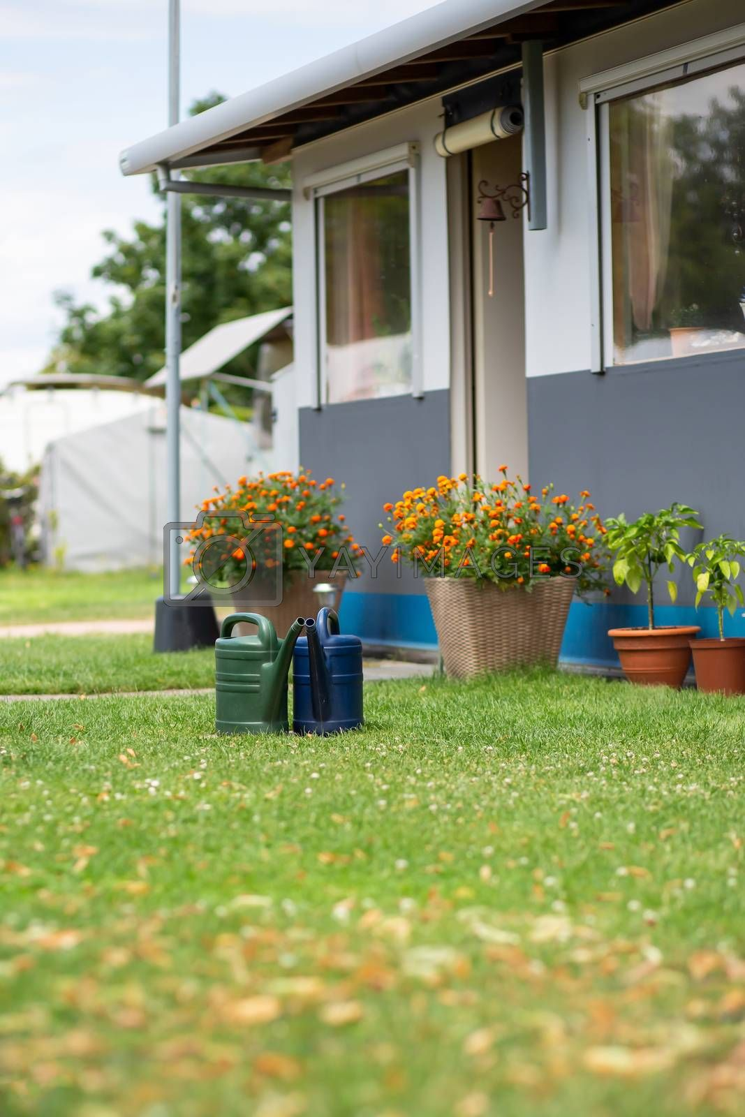 Two watering cans are standing in the meadow at a campsite by Sandra Fotodesign