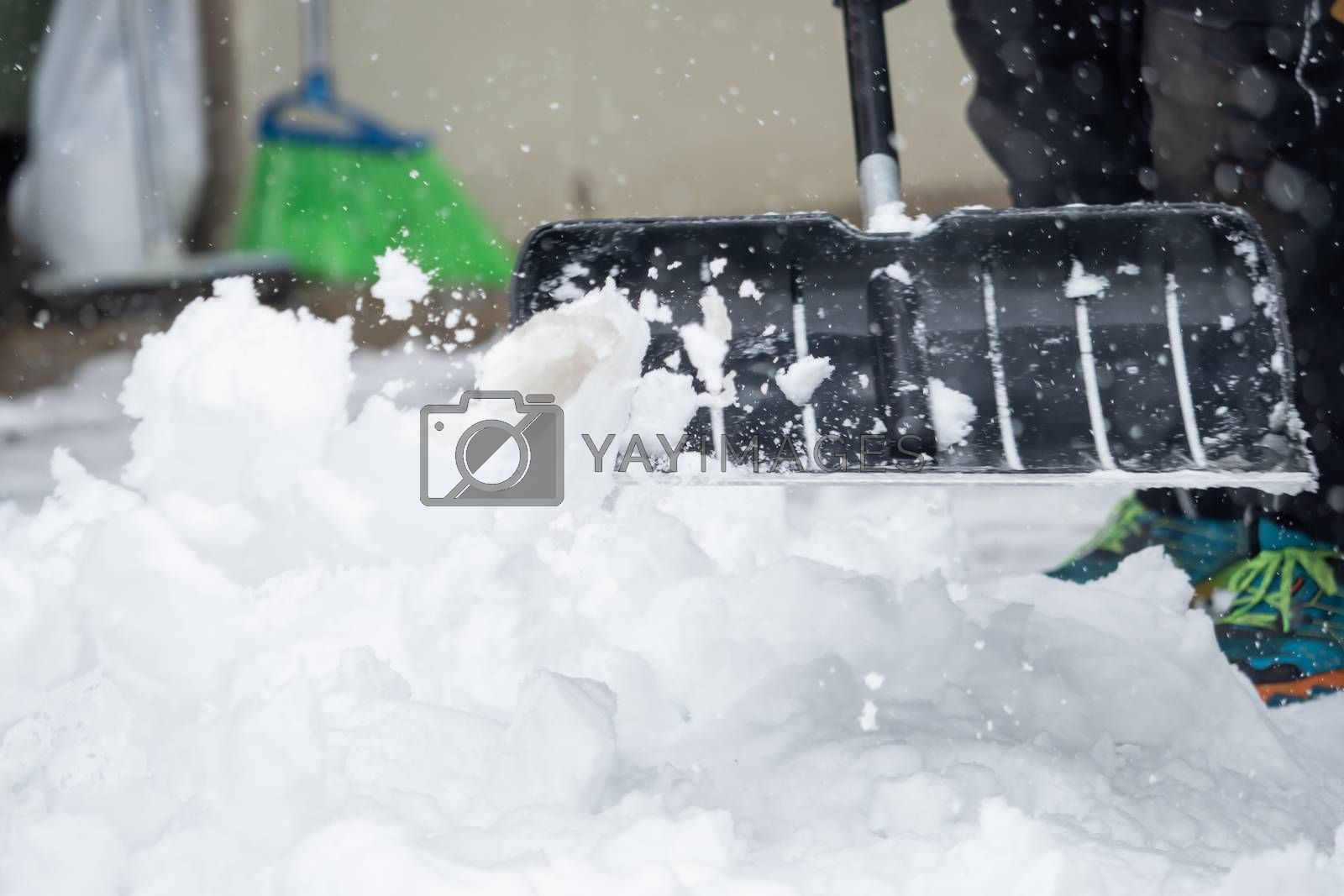 Someone is  shoveling snow outside in winter while it is snowing by Sandra Fotodesign