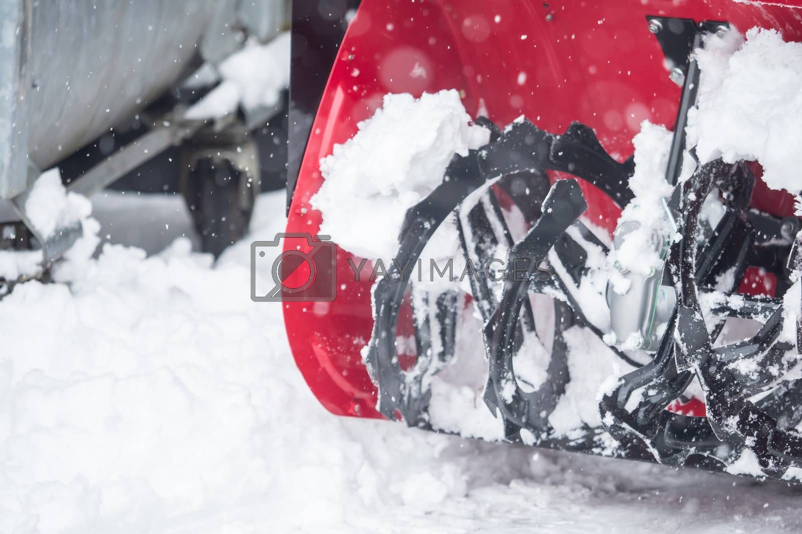 Someone uses a snowthrower outdoors in winter while it is snowin by Sandra Fotodesign
