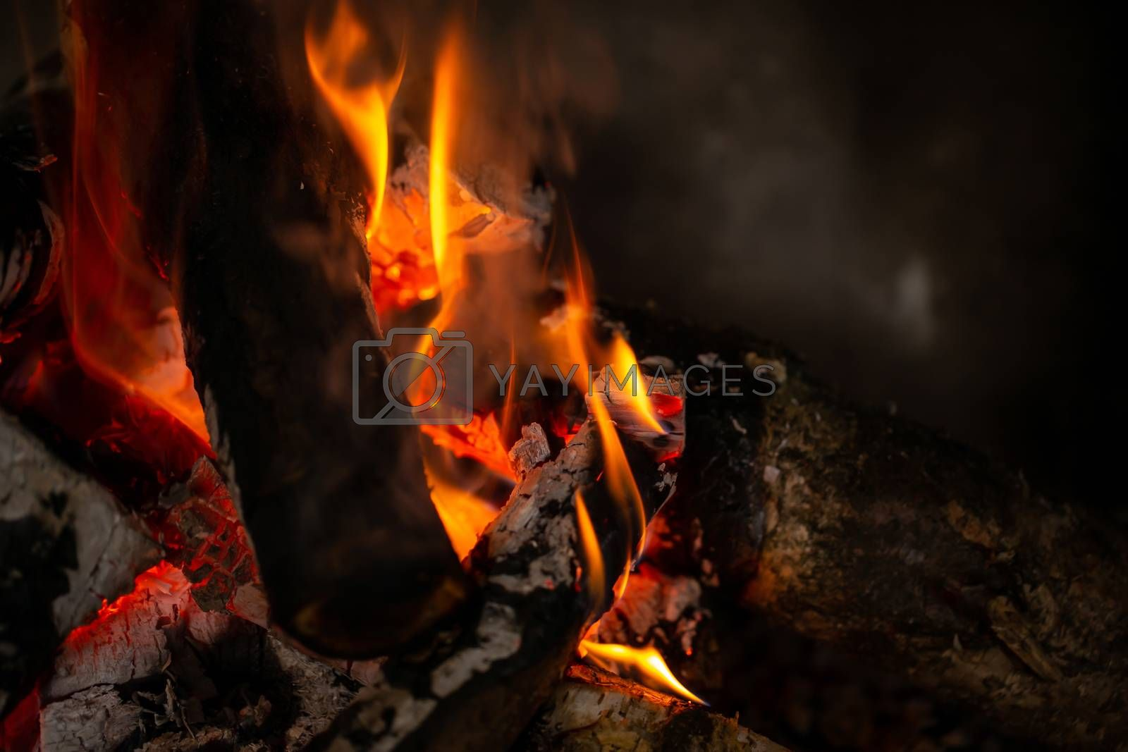 A fire is burning in the fireplace, slowly coal is being produce by Sandra Fotodesign