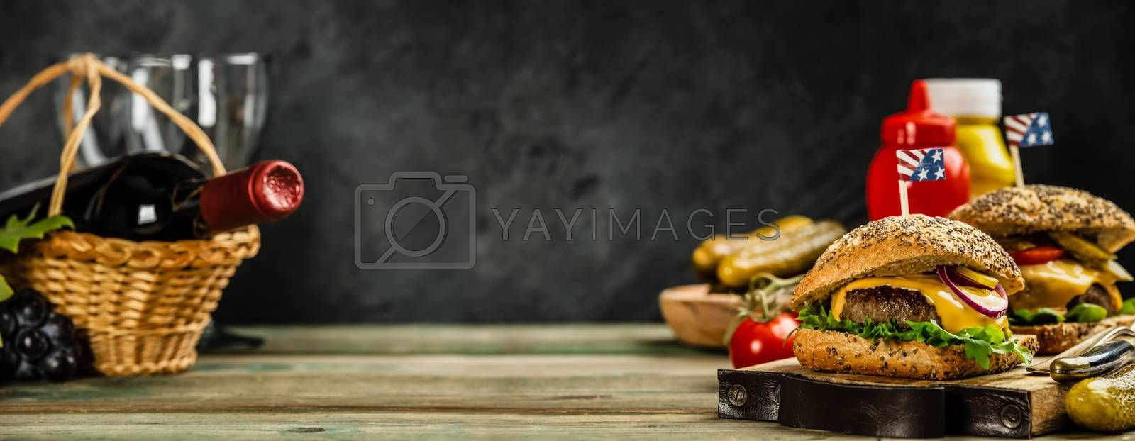 Homemade beef and ciabatta hamburgers on wooden background, space for text