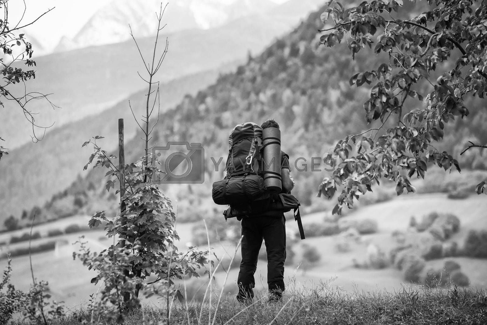 A hiker with a backpack looks into the distance by Sandra Fotodesign