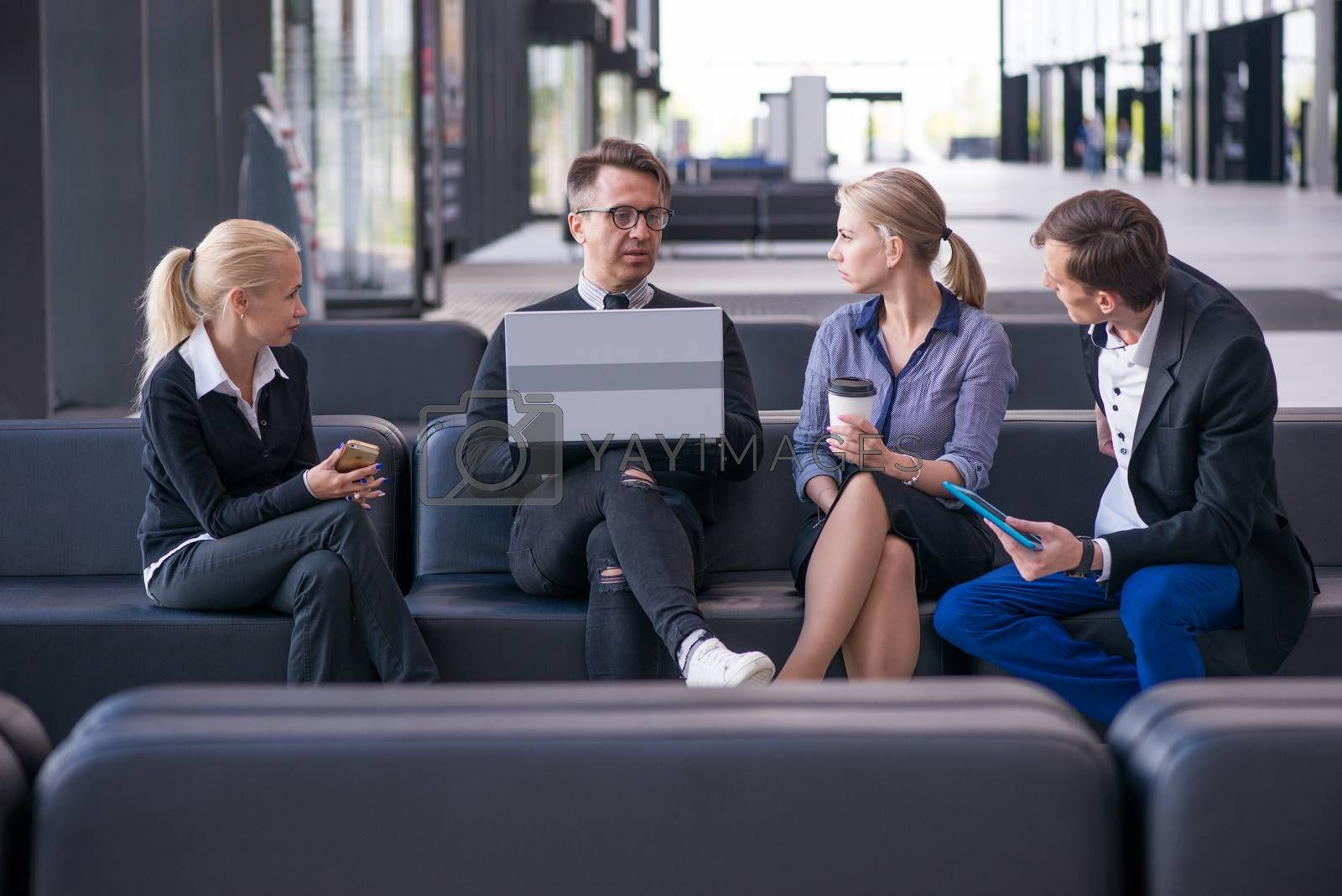 Portrait of happy business people talking at break in office lobby sitting together at sofa