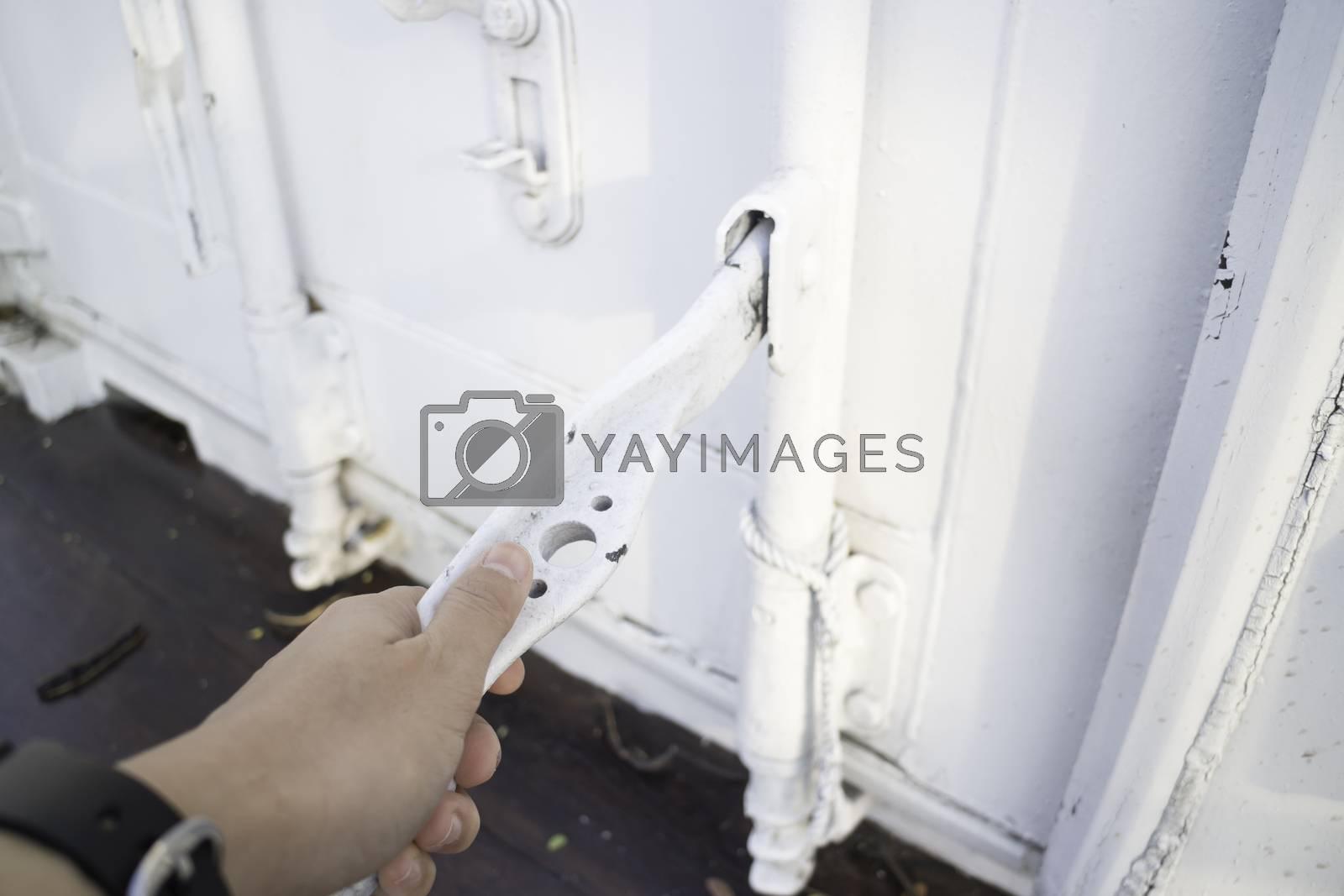 Hand on cargo container door by nalinratphi