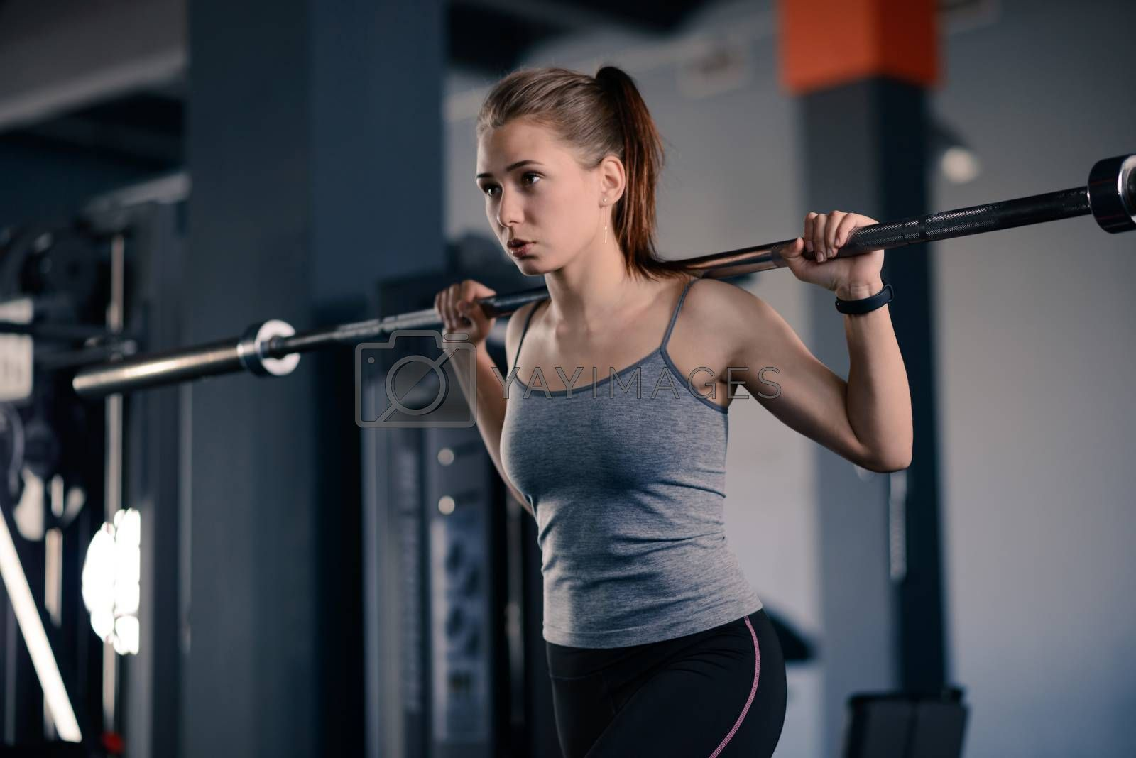 Attractive Young Sports Woman Doing Lunges with Barbell in the Gym. Fitness and Healthy Lifestyle Concept.