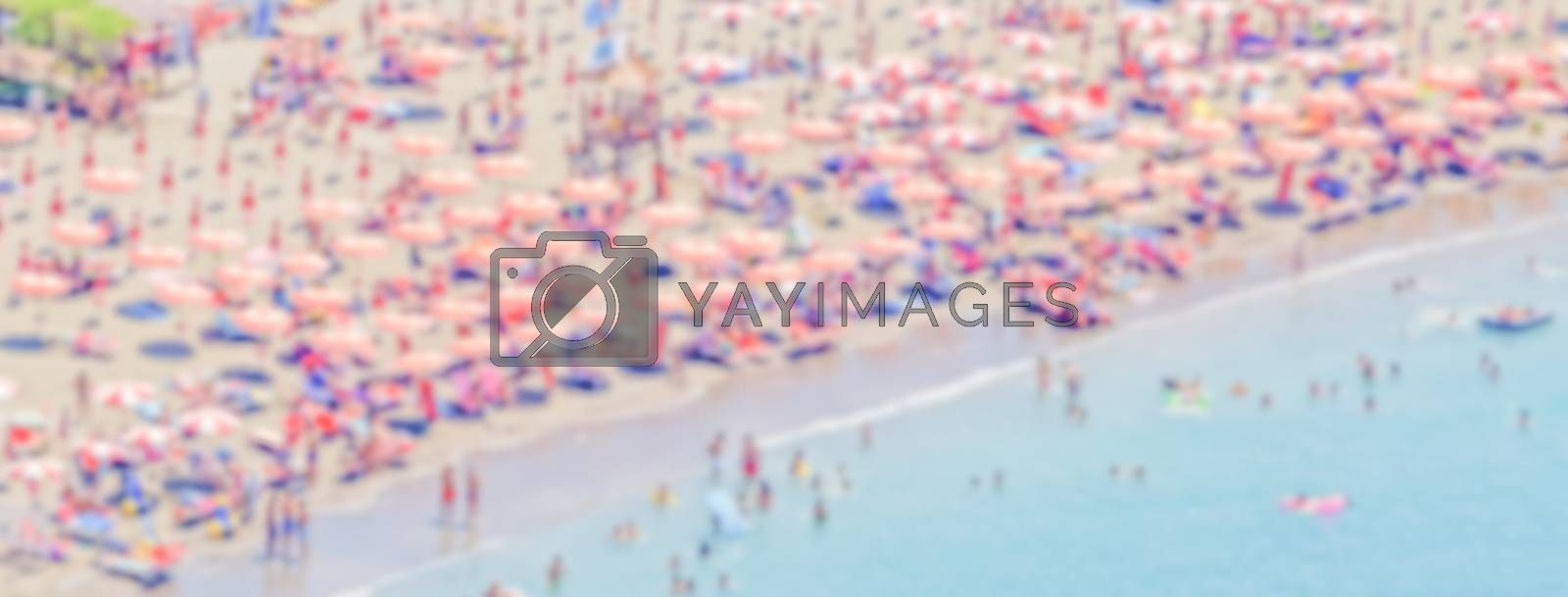 Defocused background with a crowded beach in  Italy. Intentionally blurred post production for bokeh effect