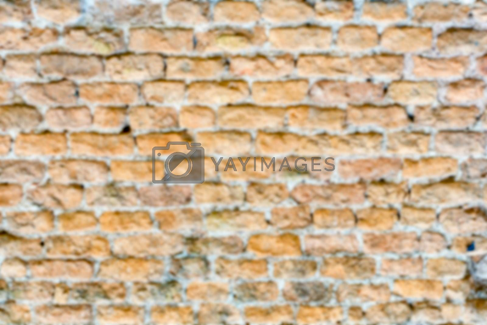 Defocused background of stone brick wall texture with copy space. Intentionally blurred post production for bokeh effect