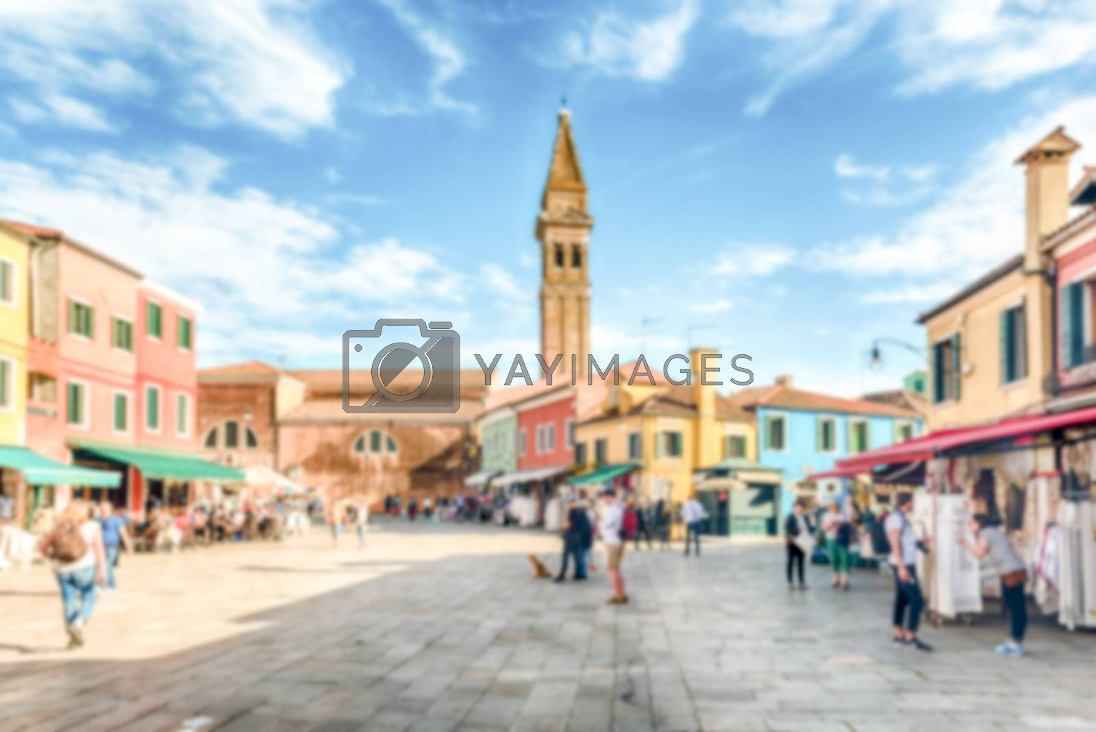 Defocused background of tourists walking on the main square of Burano island, Venice, Italy. Intentionally blurred post production for bokeh effect