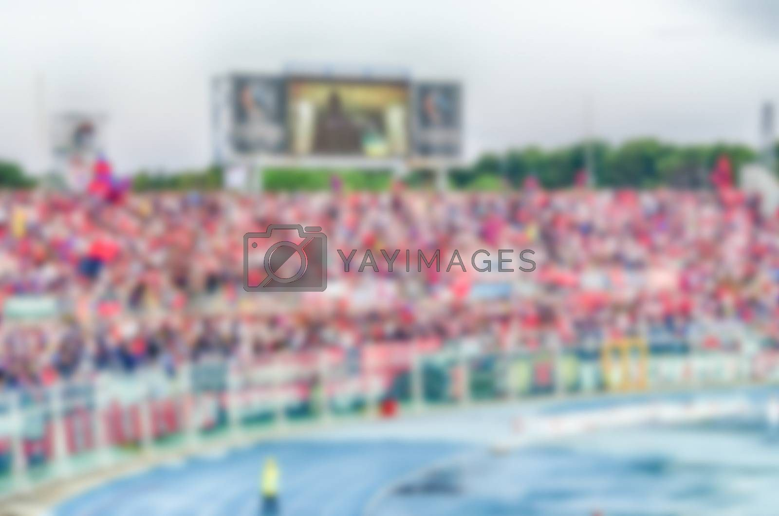 Defocused background with supporters in the stadium for football match. Intentionally blurred post production for bokeh effect