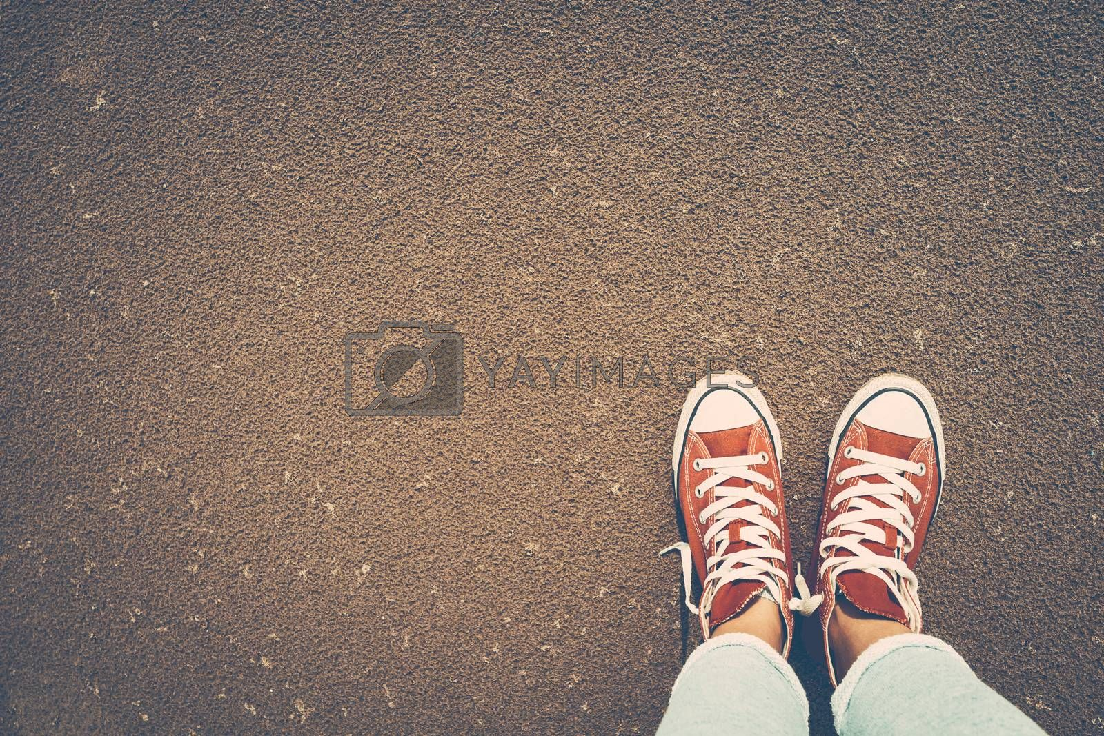 Photo of a red gumshoes over sand background, stylish shoes for active people, urban youth lifestyle
