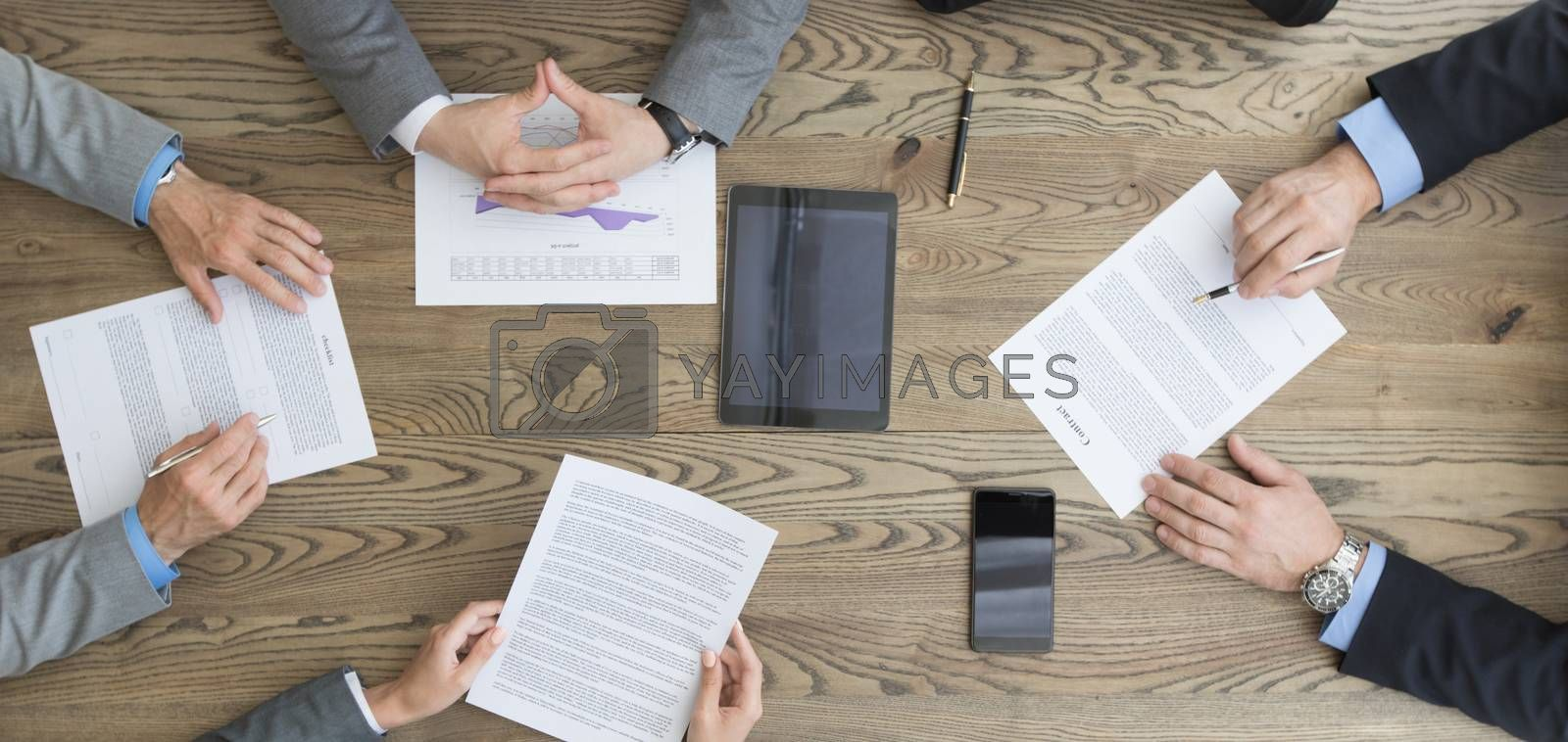 Business team working with contract, financial reports and mobile devices dicussing deal sitting around office table