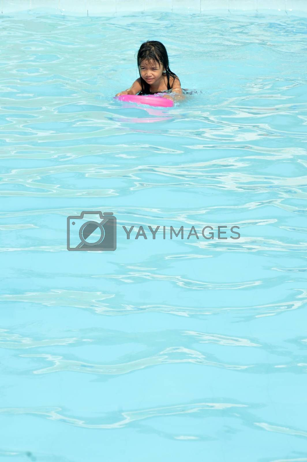 asian little girl playing in the pool by antonihalim