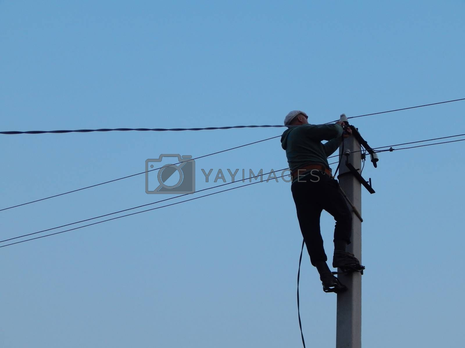Electrician works in special clothes on the pole by Prokopenko