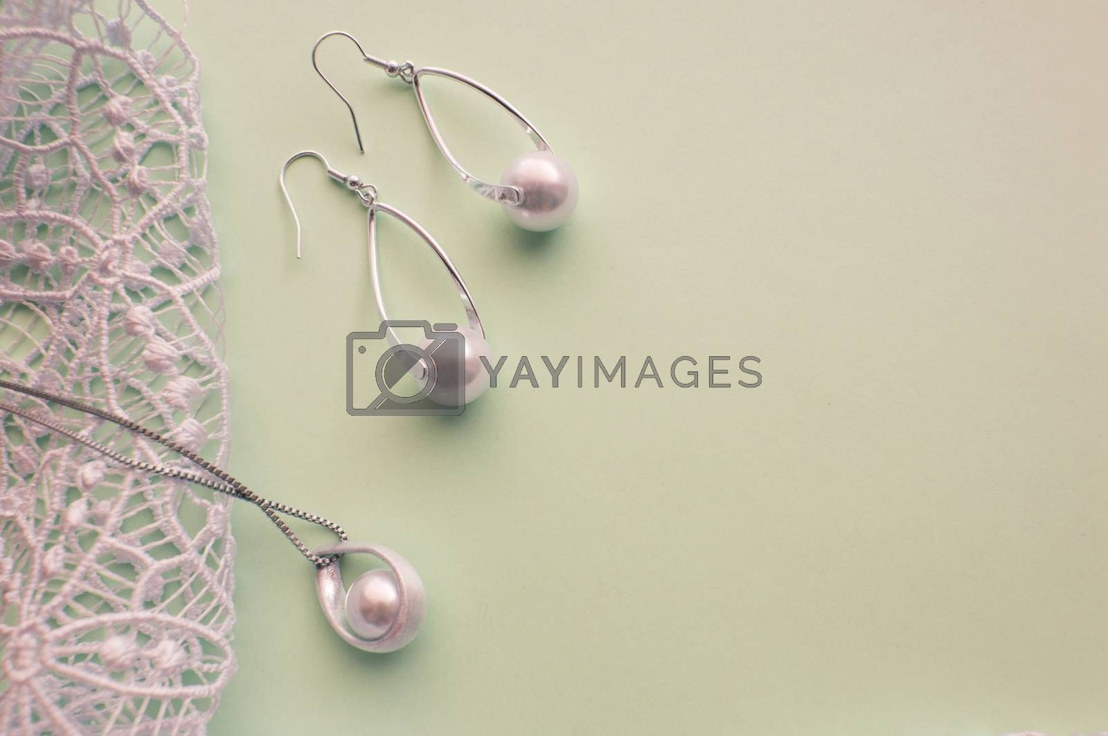 Fashion women's silver accessories - earrings and pendant with pearls on light background with rich openwork lace, top view, flat, space for text by Claire Lucia