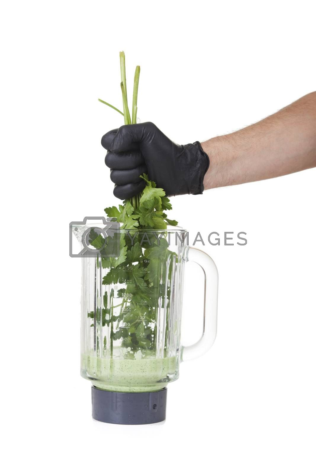 hand holding herbs in a mixer  by bernjuer