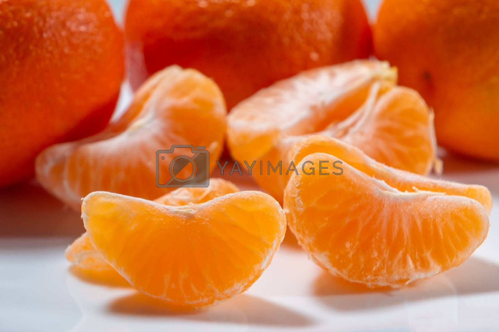 Several whole and peeled ripe tangerines on a white plate by galsand