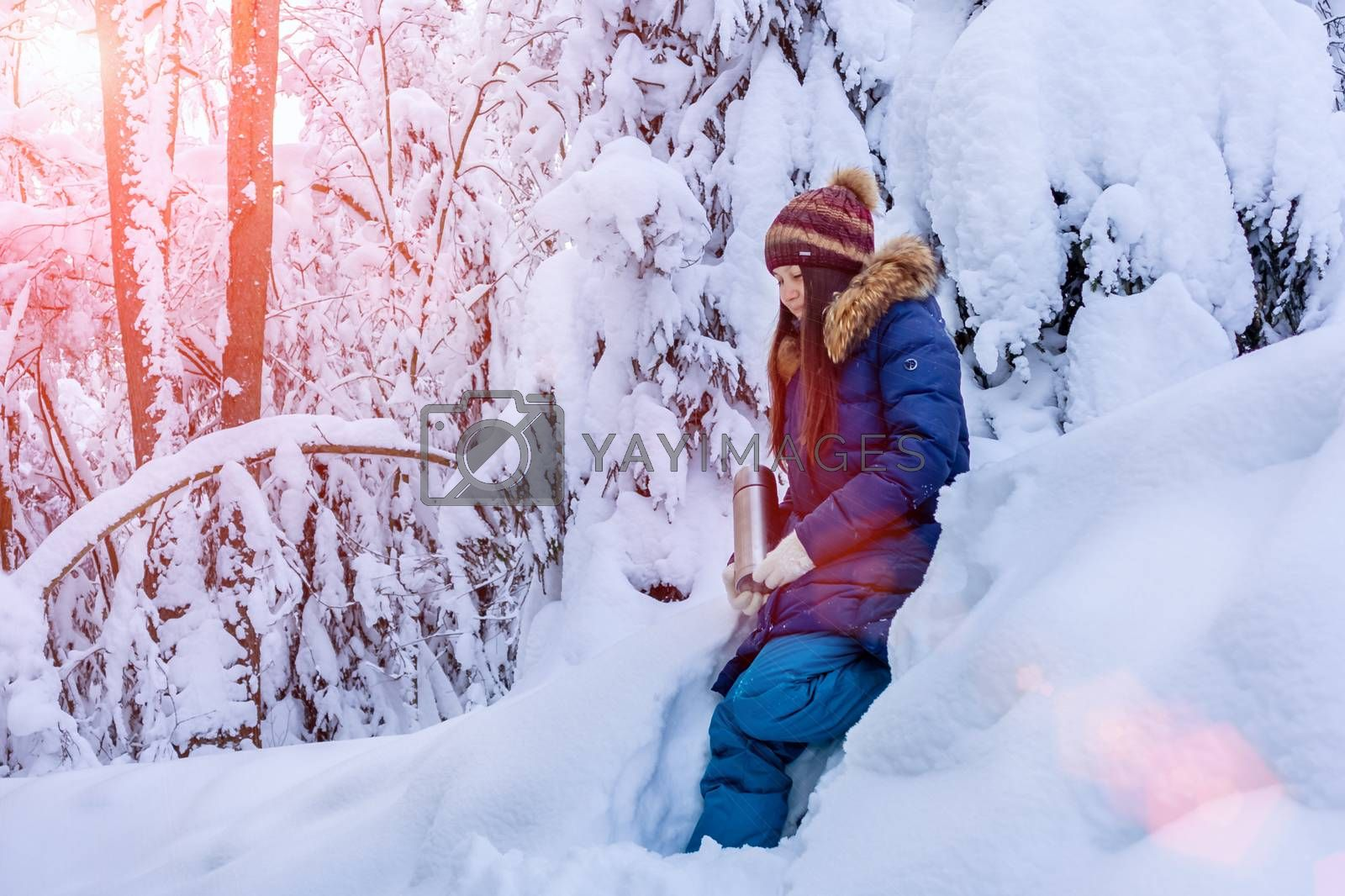 girl with a thermos in her hands is walking in the snowy winter forest by galsand