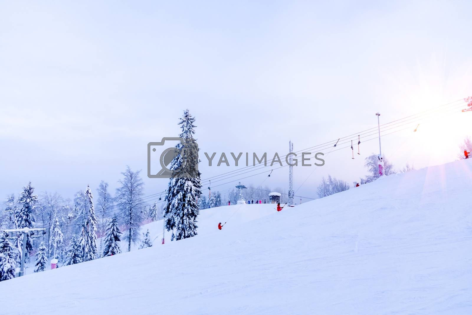 Snow-covered ski slope in the mountains with a lift and skiers skating away by galsand