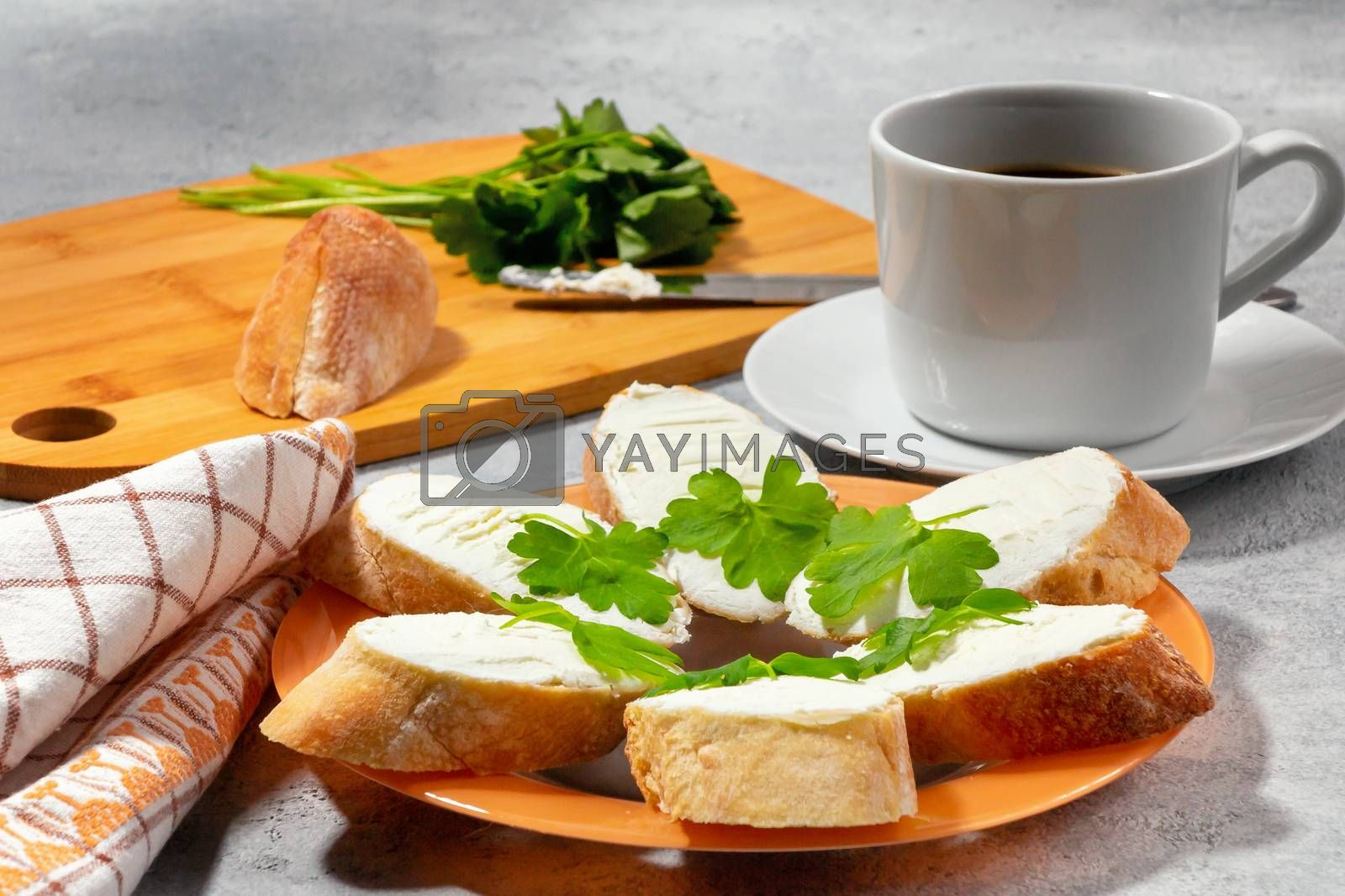 Freshly made sandwiches with cream cheese and parsley on a plate, chopping wooden board and a cup of coffee - morning and breakfast concept by galsand