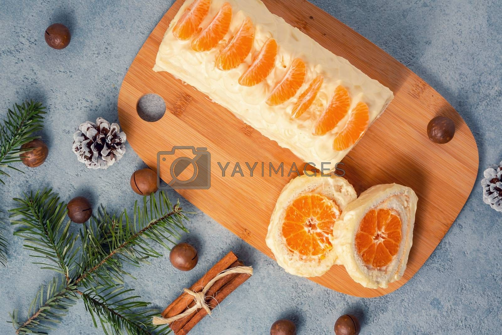 Sweet roll with whipped cream and tangerine filling and Christmas decorations by galsand
