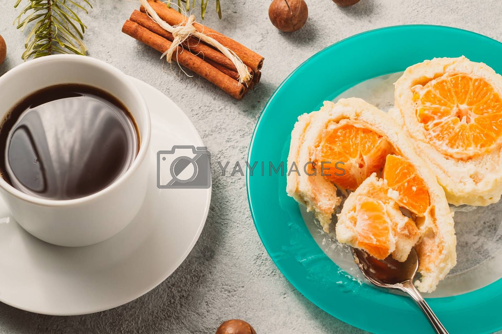 Sweet roll with whipped cream and tangerine filling and Christmas decorations and a cup of coffee by galsand