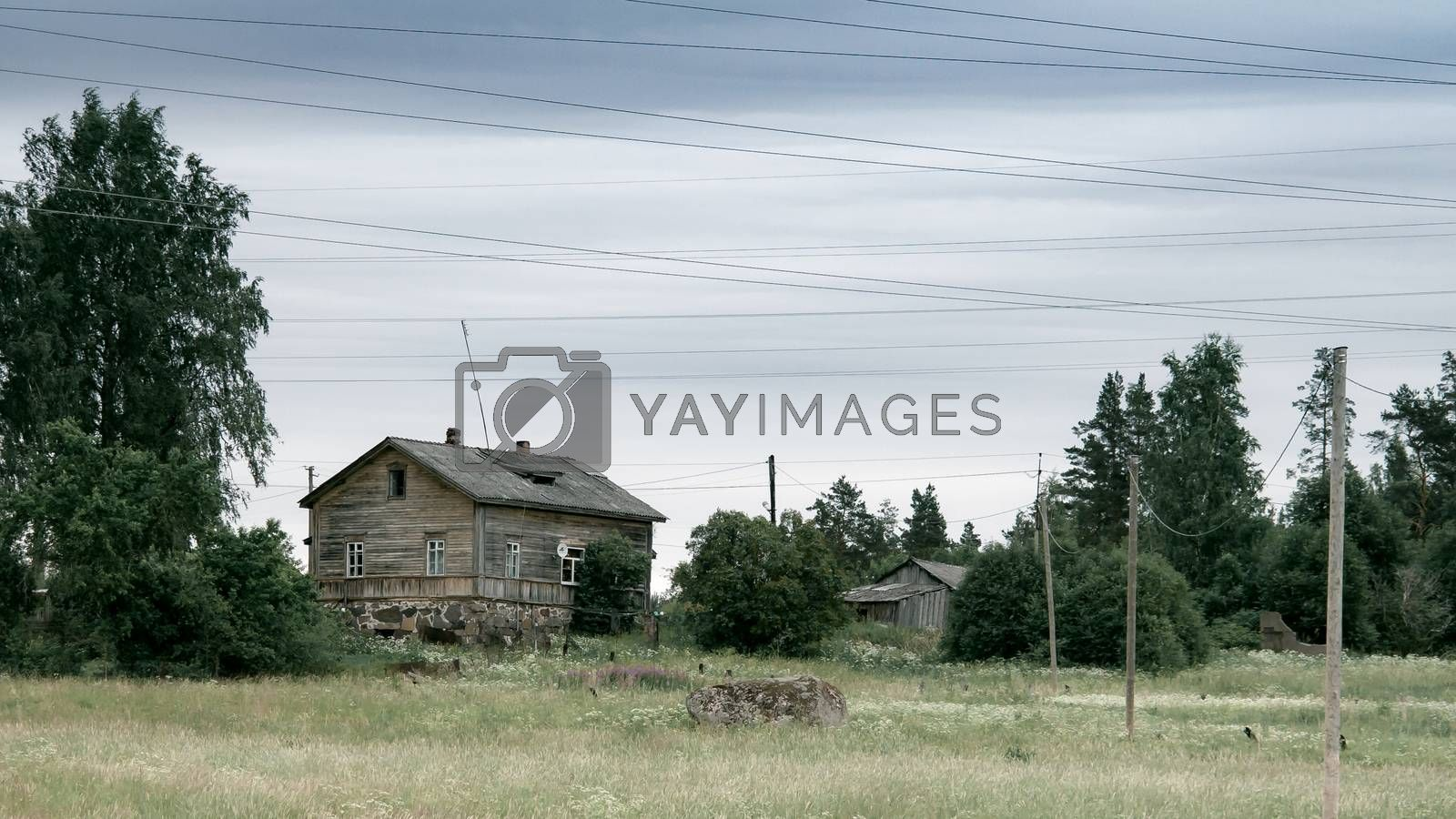 Old wooden house in the meadow. Stone foundation. Rural landscape by galsand