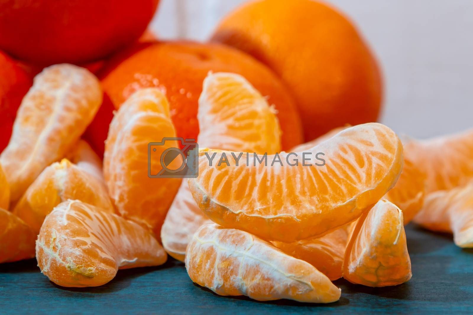 few peeled tangerine slices on the turquoise surface of the table, space for text by galsand