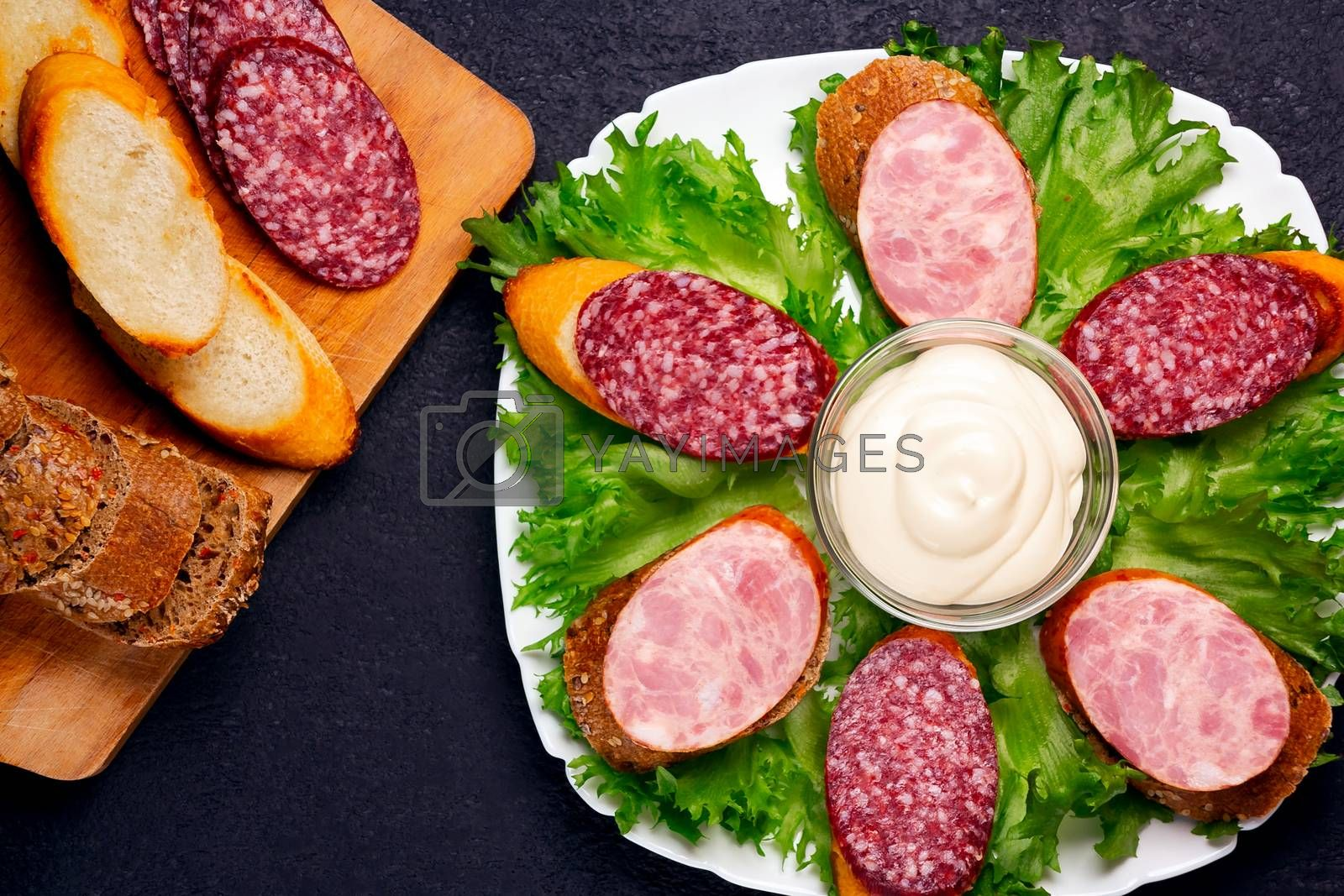 Several sandwiches with sausage and salami and sauce on a plate, flat lay by galsand