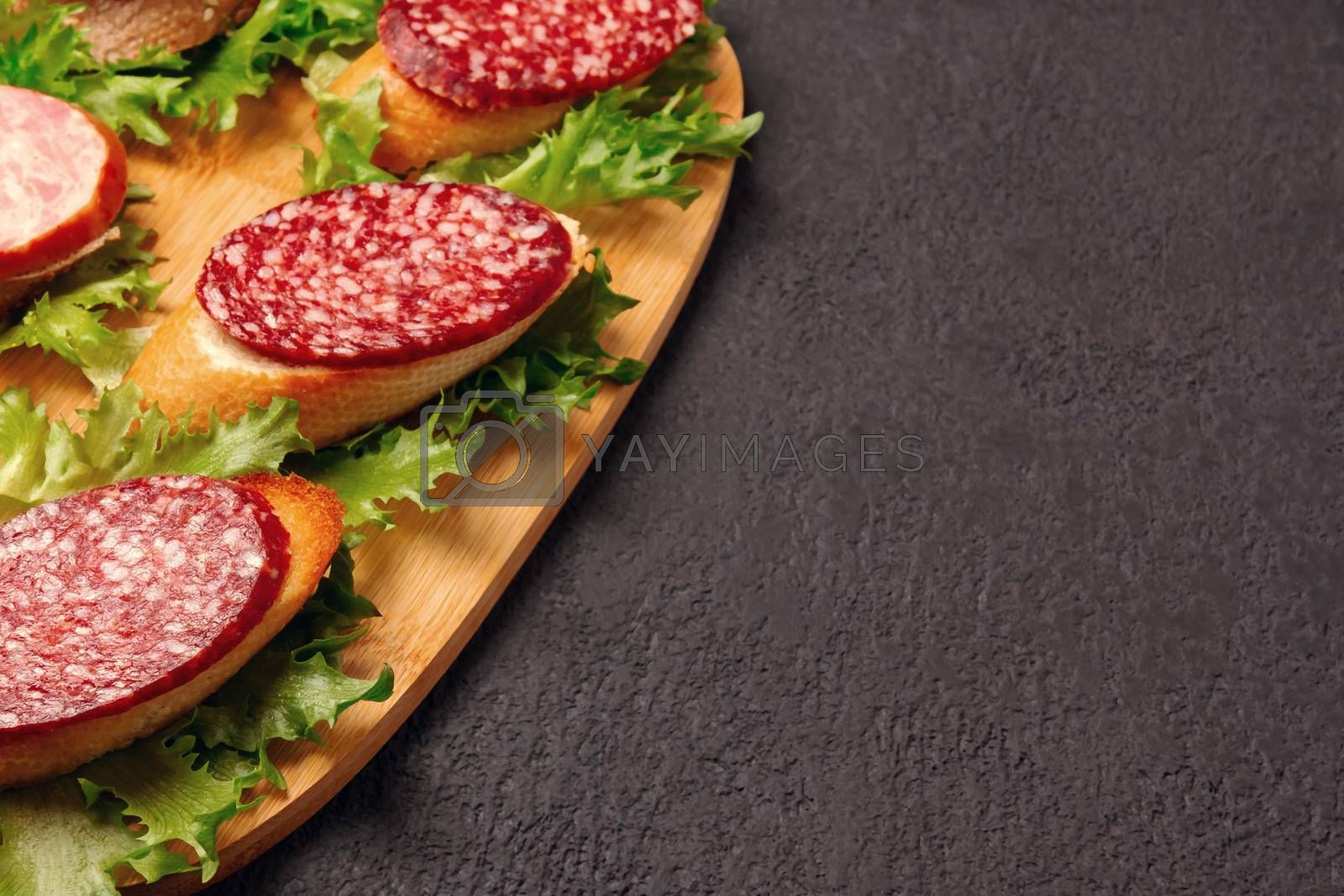 Several sandwiches with sausage and salami and sauce on a black board, background with copyspace by galsand
