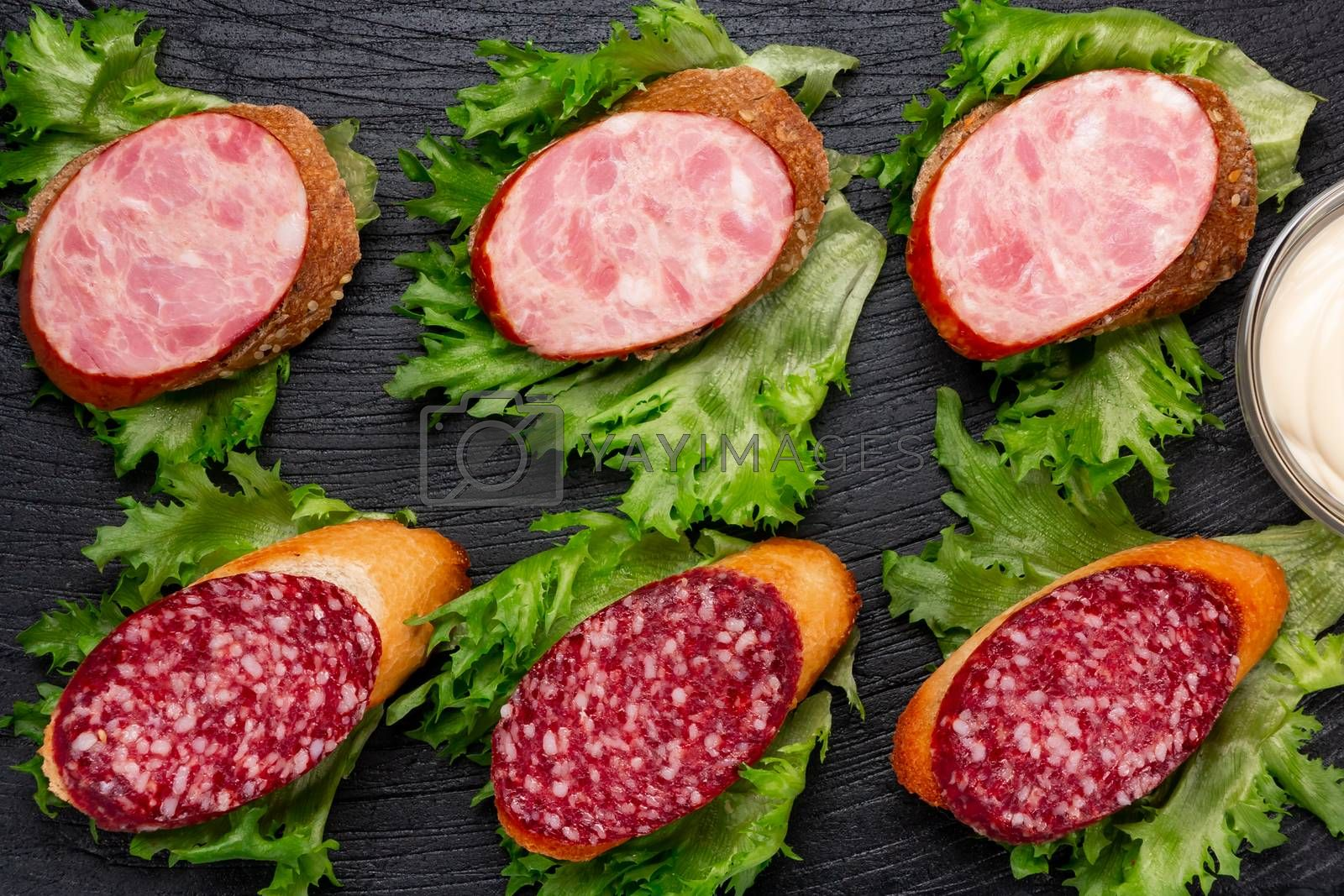 Several sandwiches with sausage and salami and sauce on a black board, flat lay by galsand