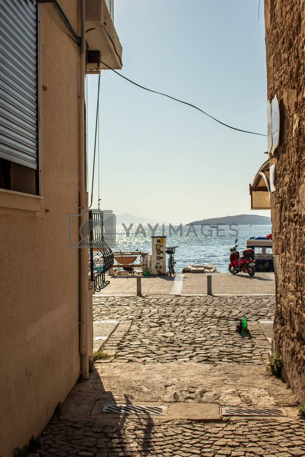 a narrow view of sea between old buildings by Swonie