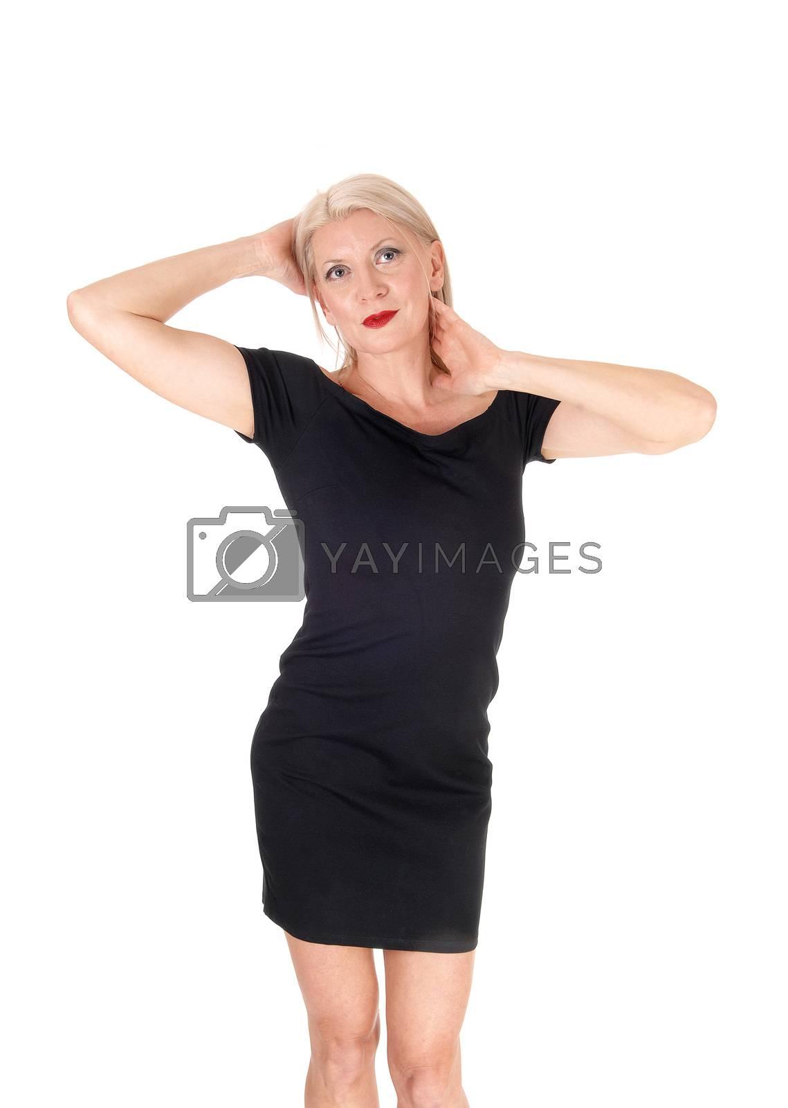 Beautiful woman standing in a short black dress hands on head by feierabend