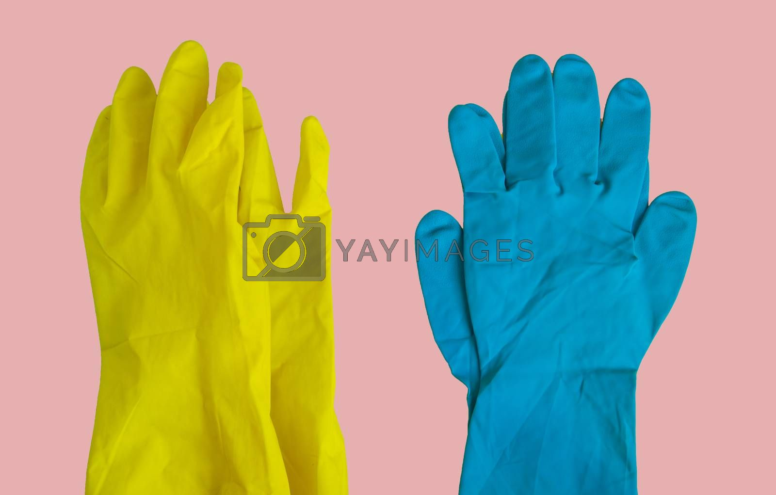 Top view of yellow and blue rubber protective gloves on pink table for spring or daily cleaning. The concept of a commercial cleaning company. by Claire Lucia