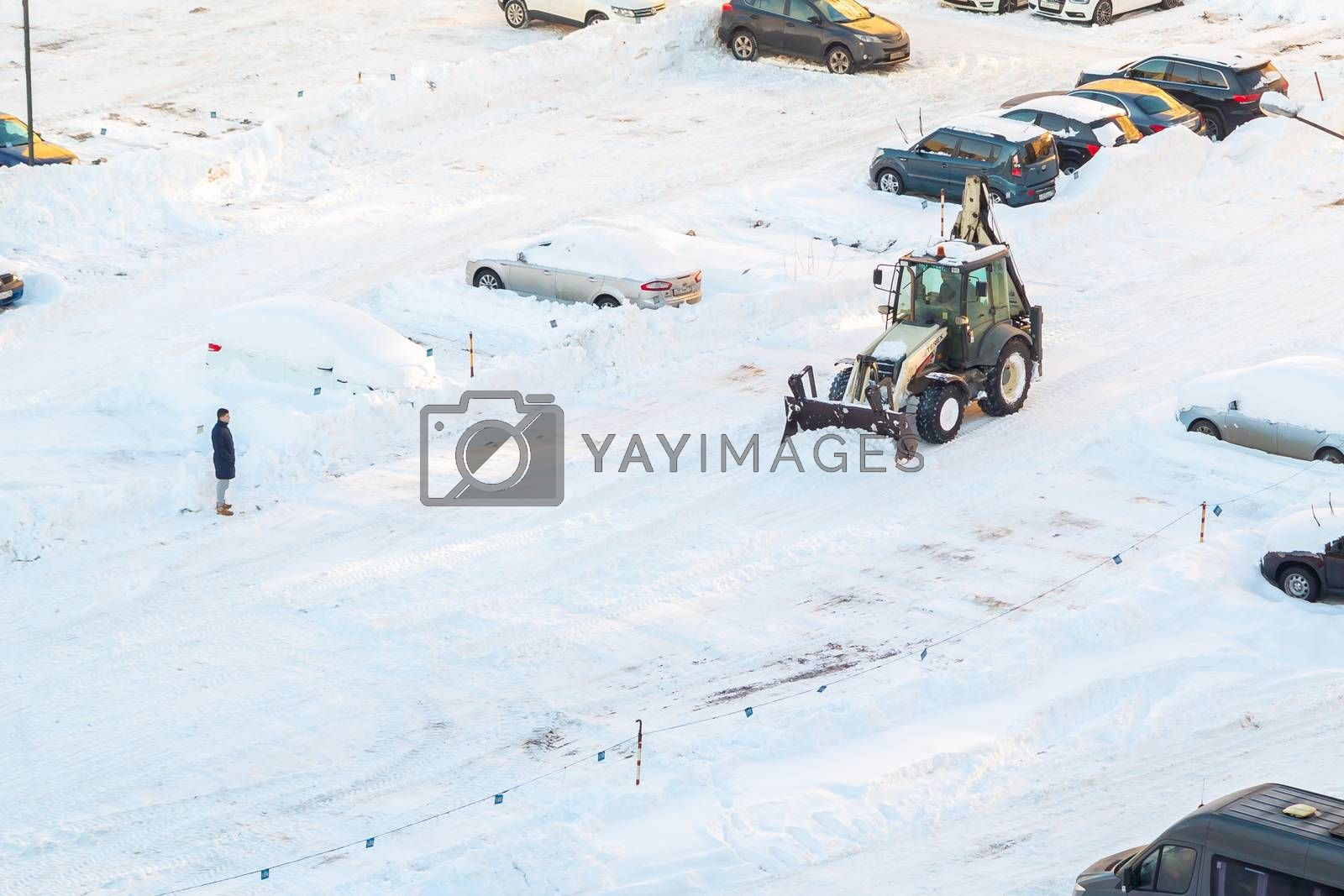 Tractor removes snow in the parking lot after a snowfall by galsand