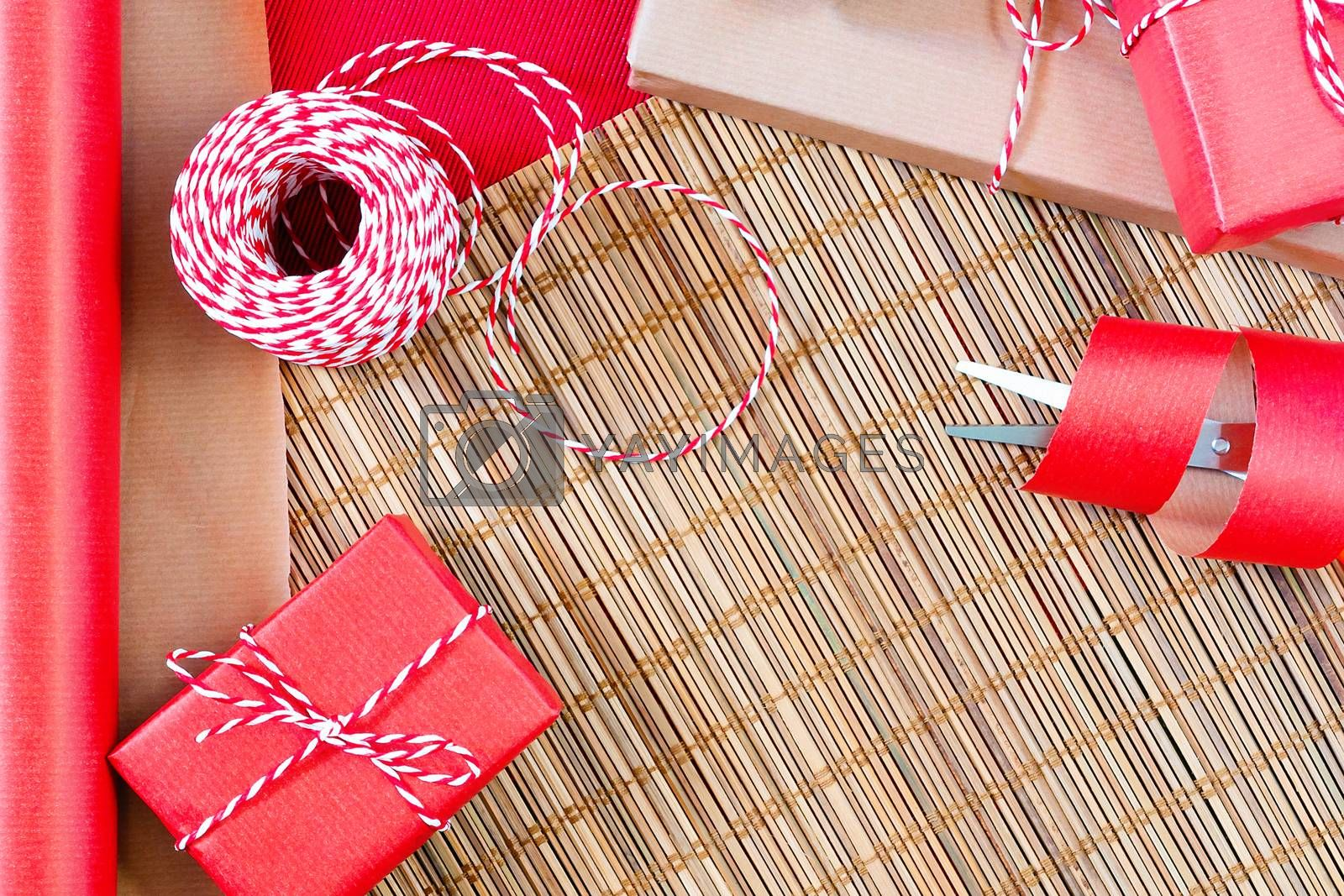 Preparing for the holiday - gift wrapping in red and beige wrapping paper by galsand
