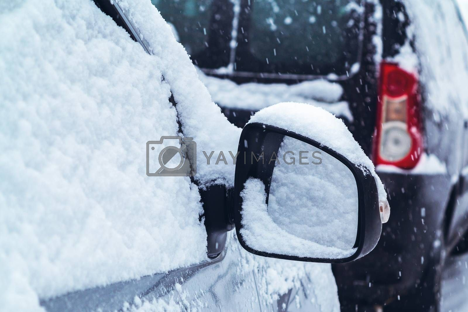 Snowfall in the city, part of the car covered by snow by galsand